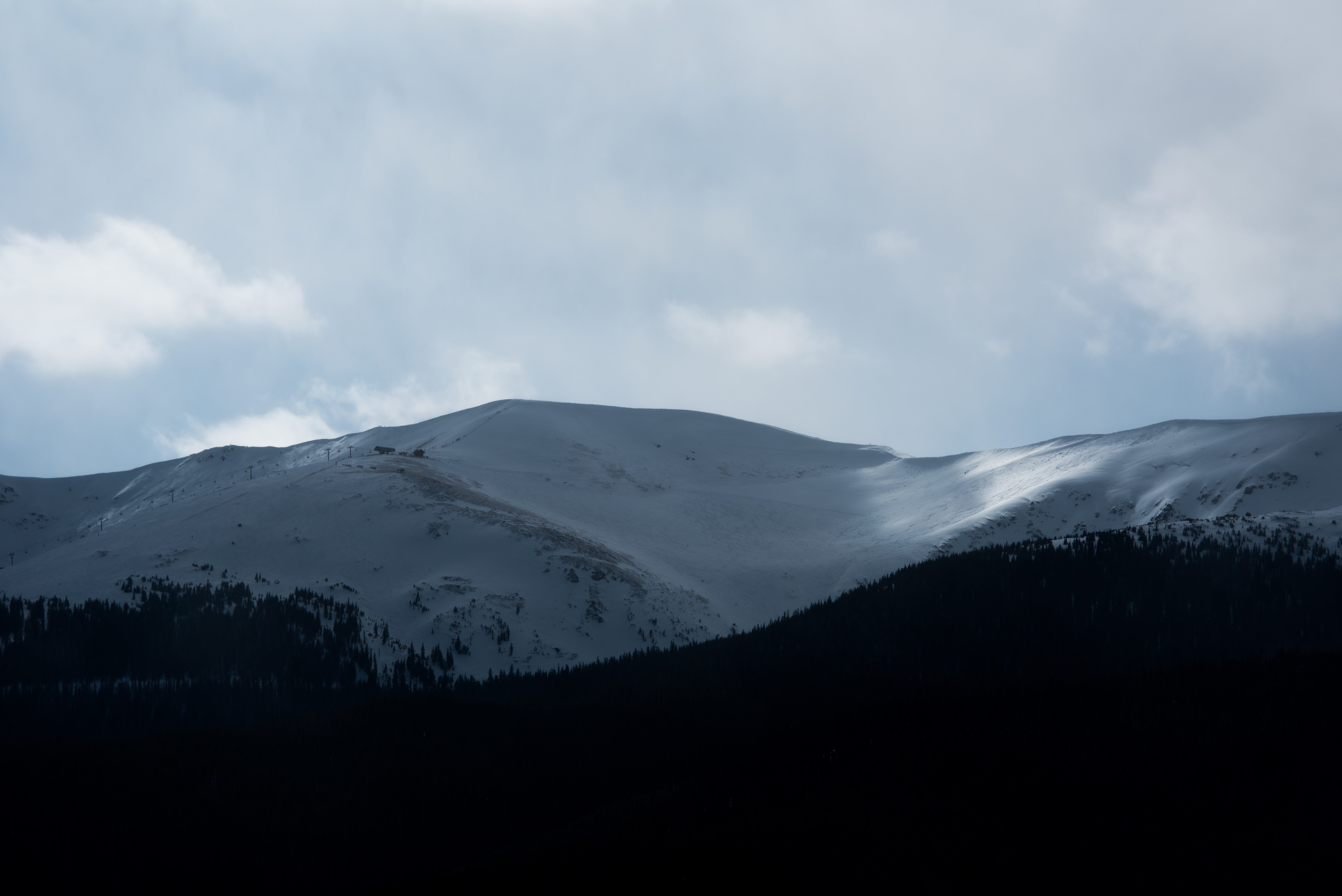 A mountain covered in snow stands tall, near the clouds