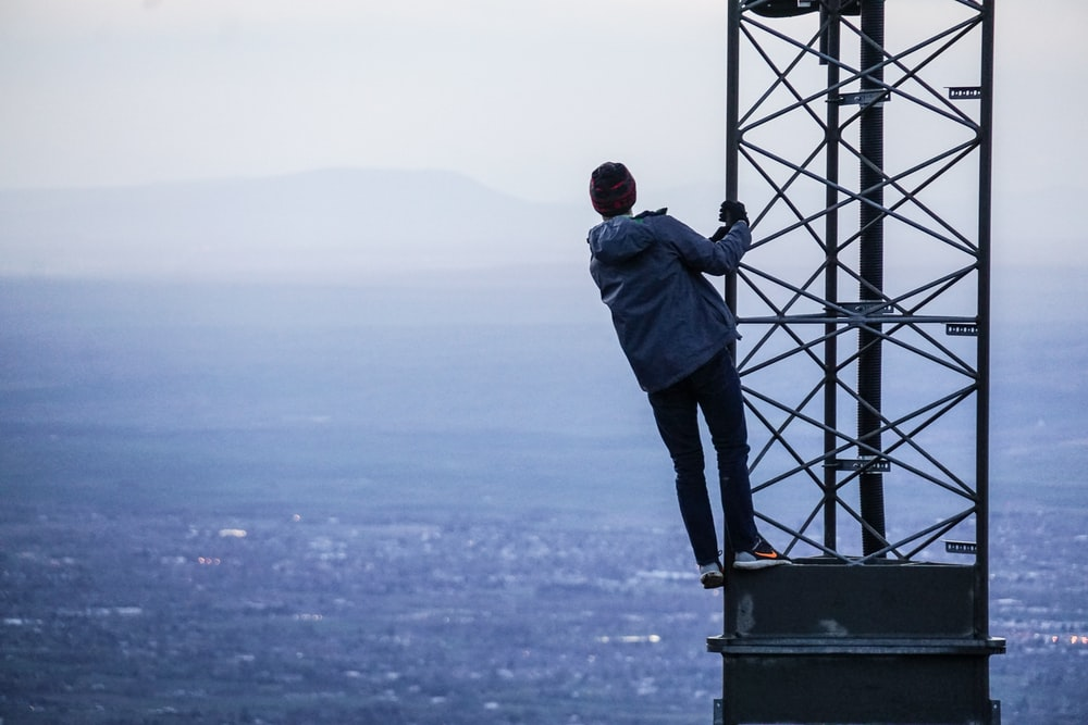man climbing on tower near buildings at daytime