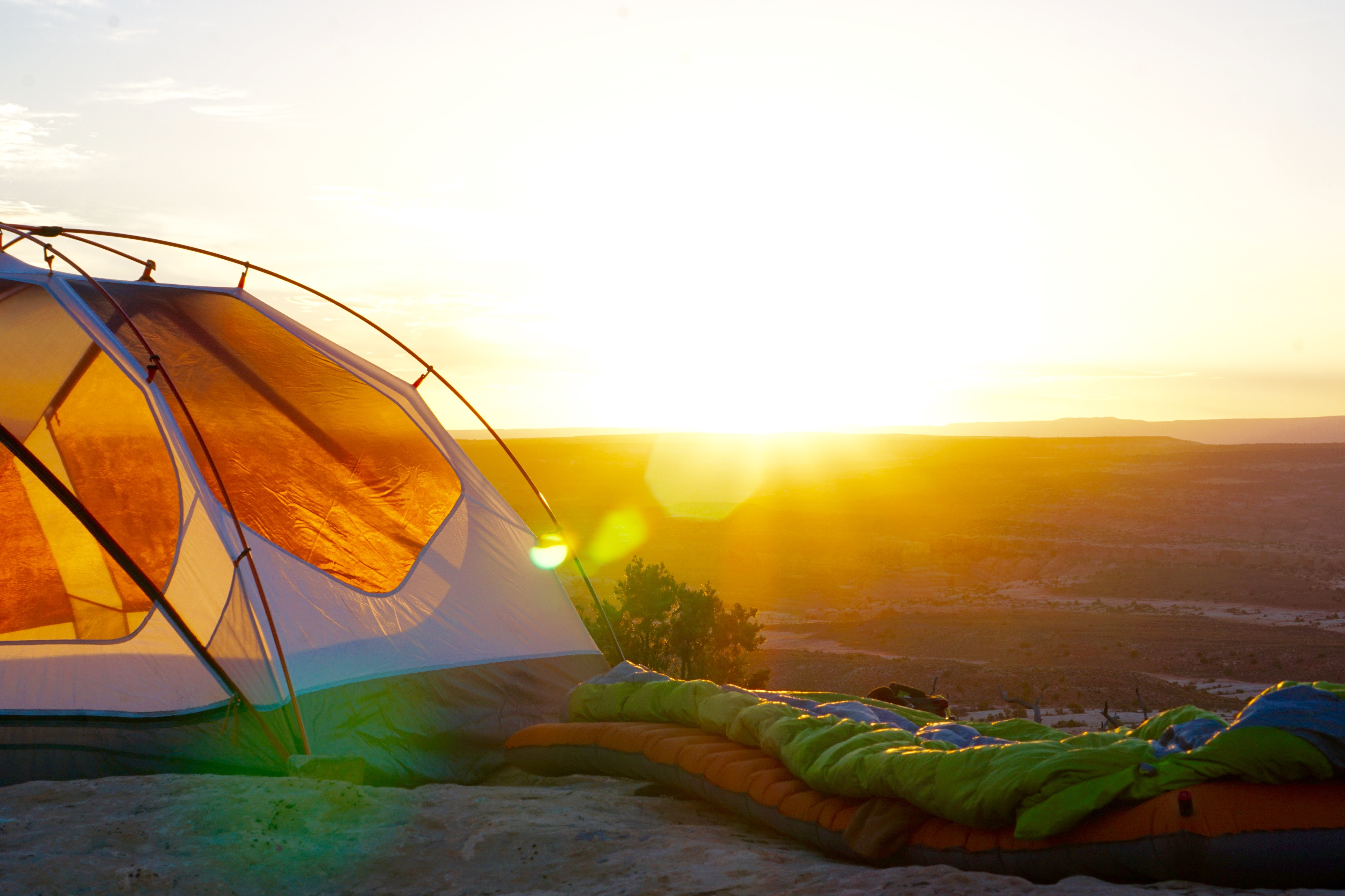 Sleeping bags next to a tent in the wilderness at sunrise