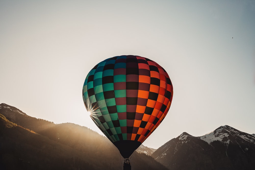 red, black, and green hot air balloon flying near mountain at daytime