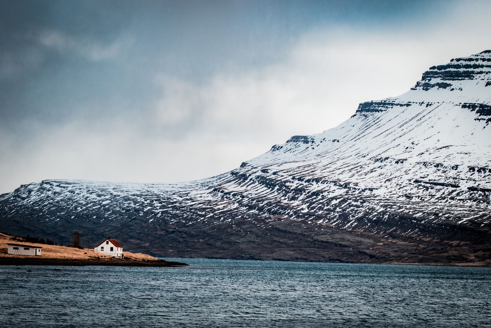 house on island near snow covered mountain at daytime