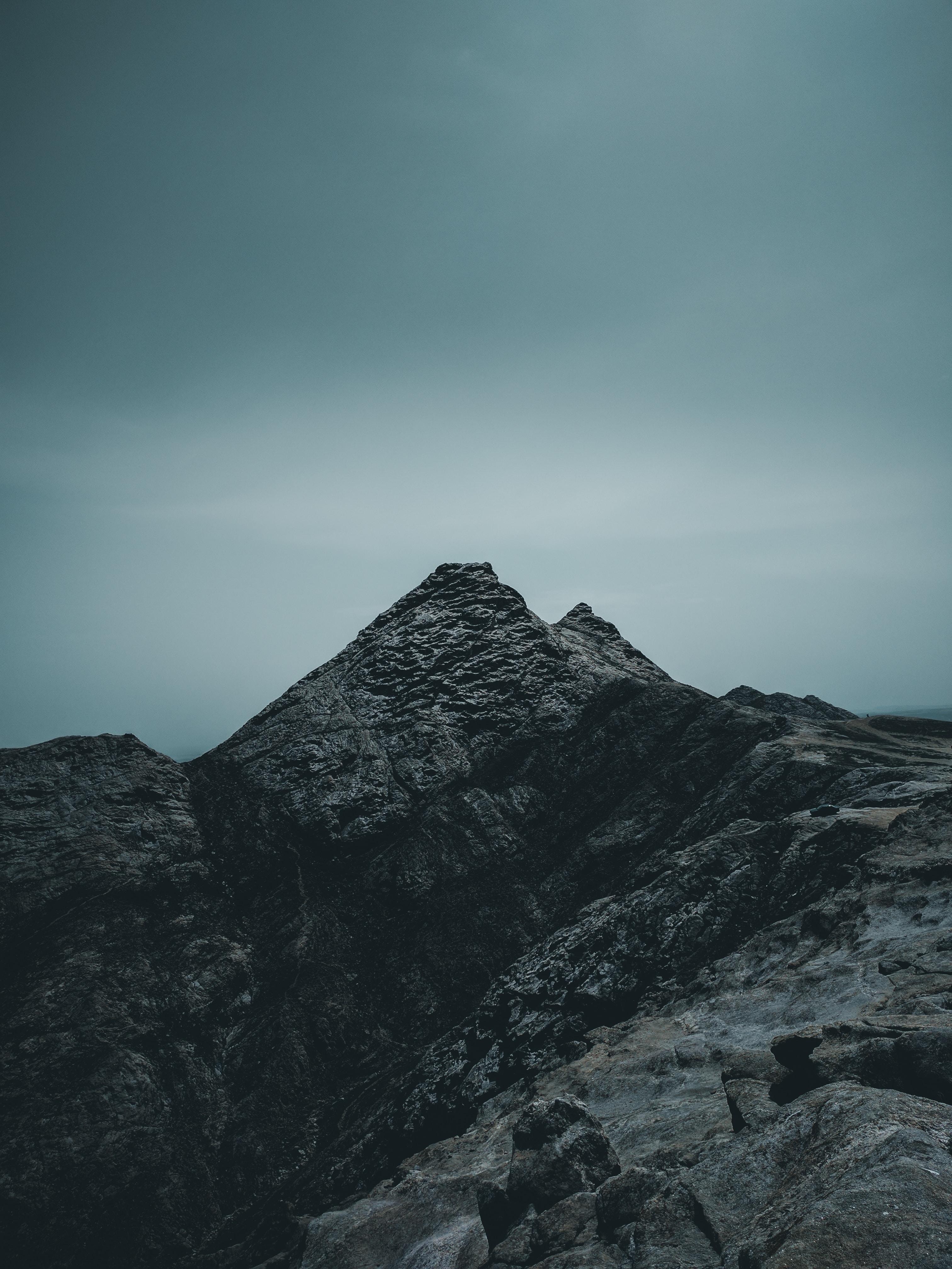 rock mountain under cloudy sky