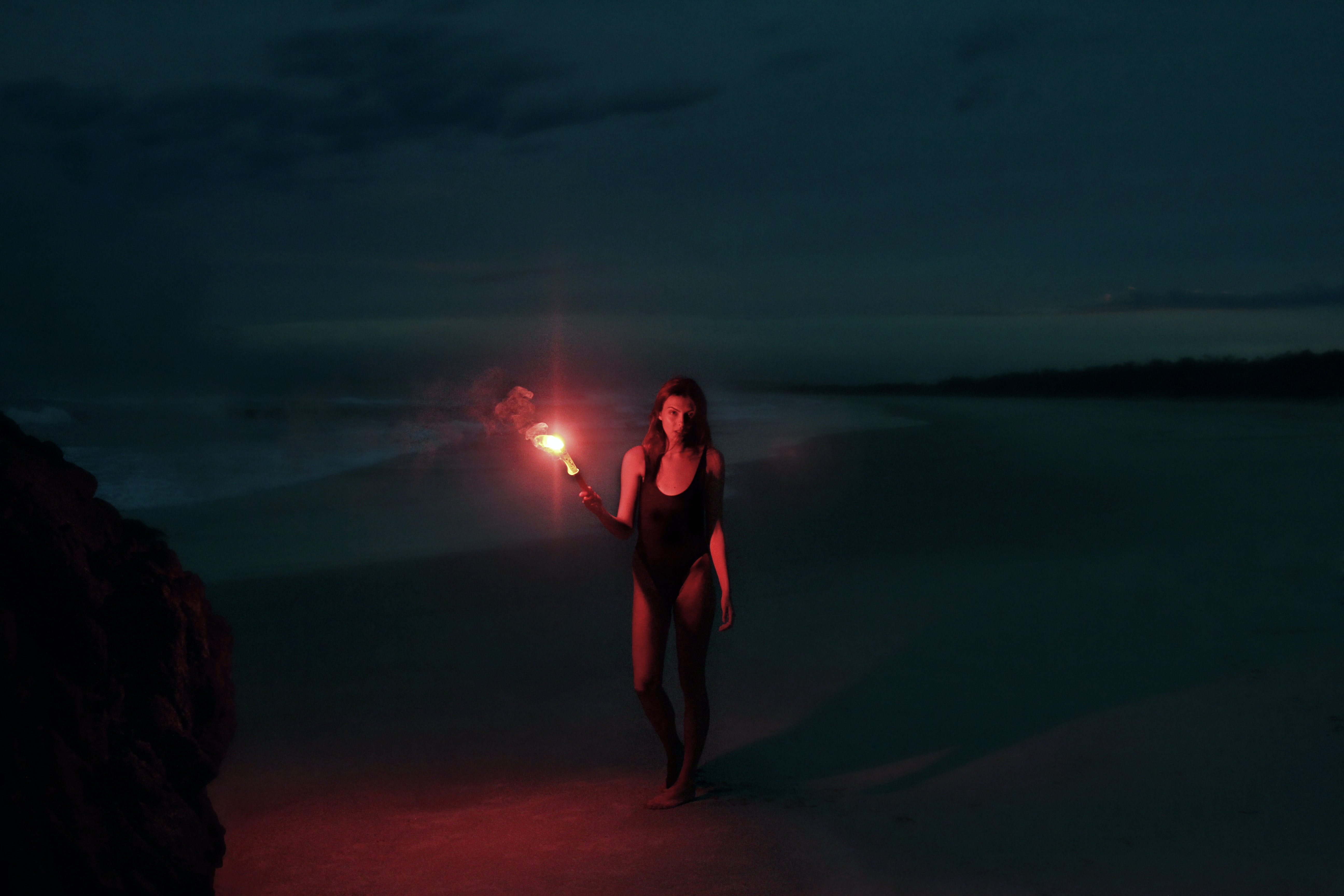 woman in one-piece swimsuit holding torch