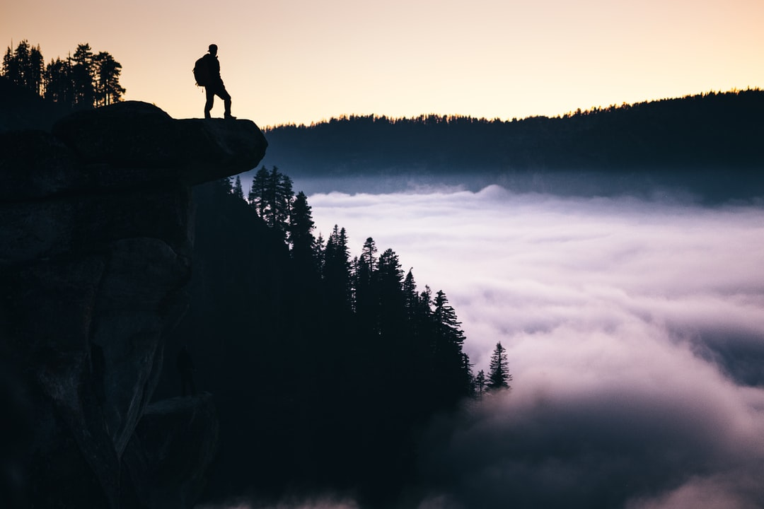 This was a very unique evening on Glacier Point in Yosemite.  The entire valley was fogged in, creating a surreal feeling of being above the clouds while still on solid ground.  I captured this image as two daring men stood out on the overhangs, just inches away from the abyss below.