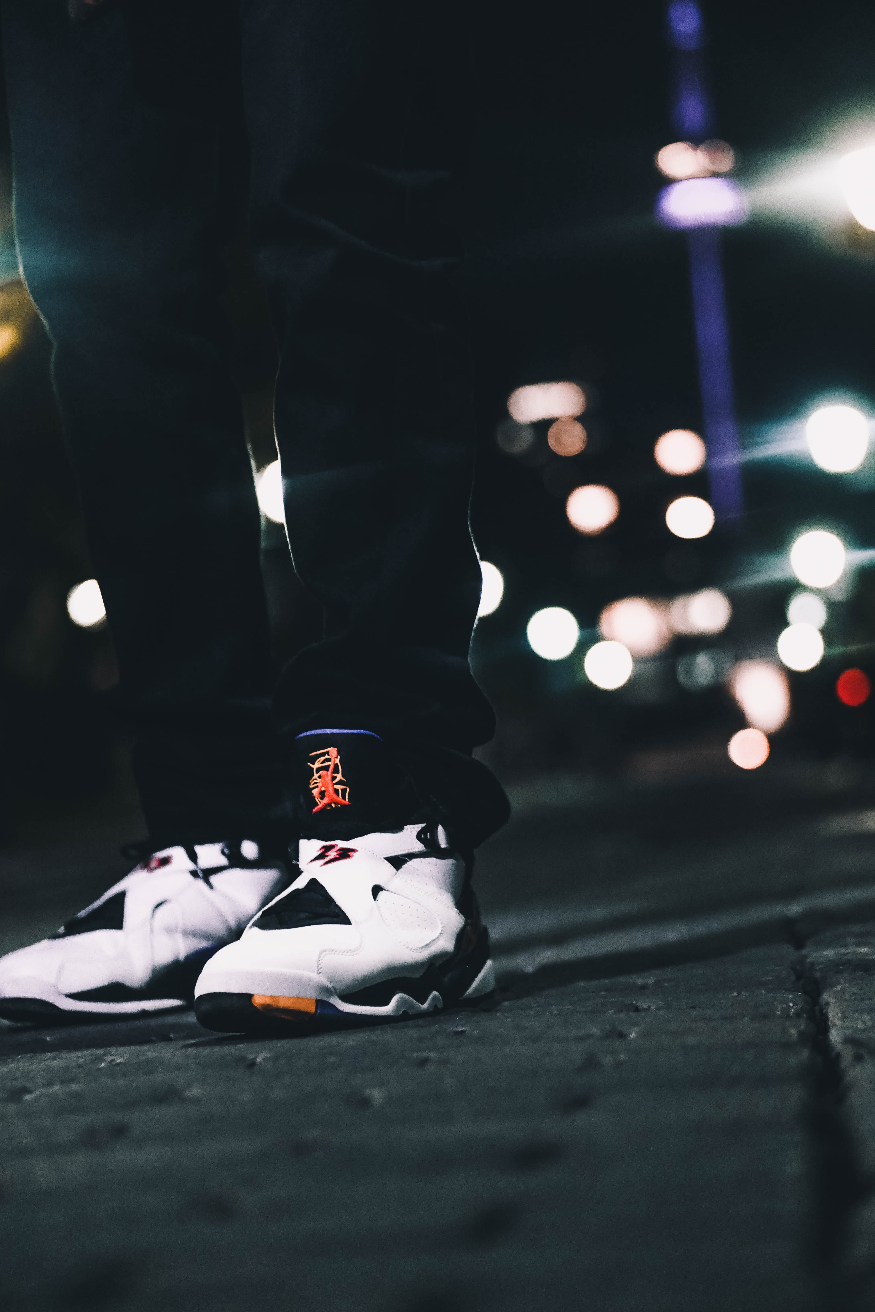 shallow focus photography of person wearing Air Jordan 8's standing on gray concrete floor