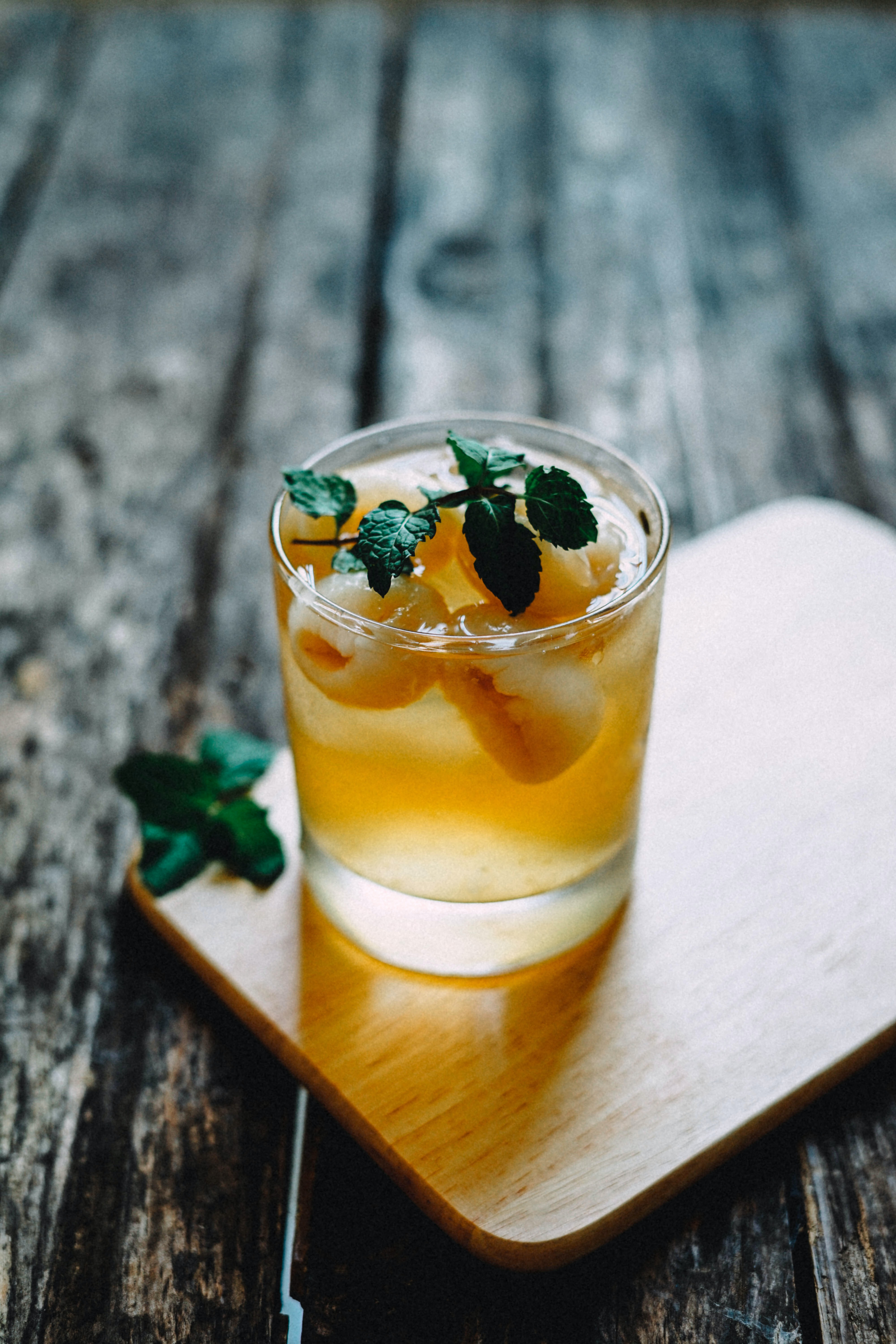 A cold cocktail whiskey with leaves on a table