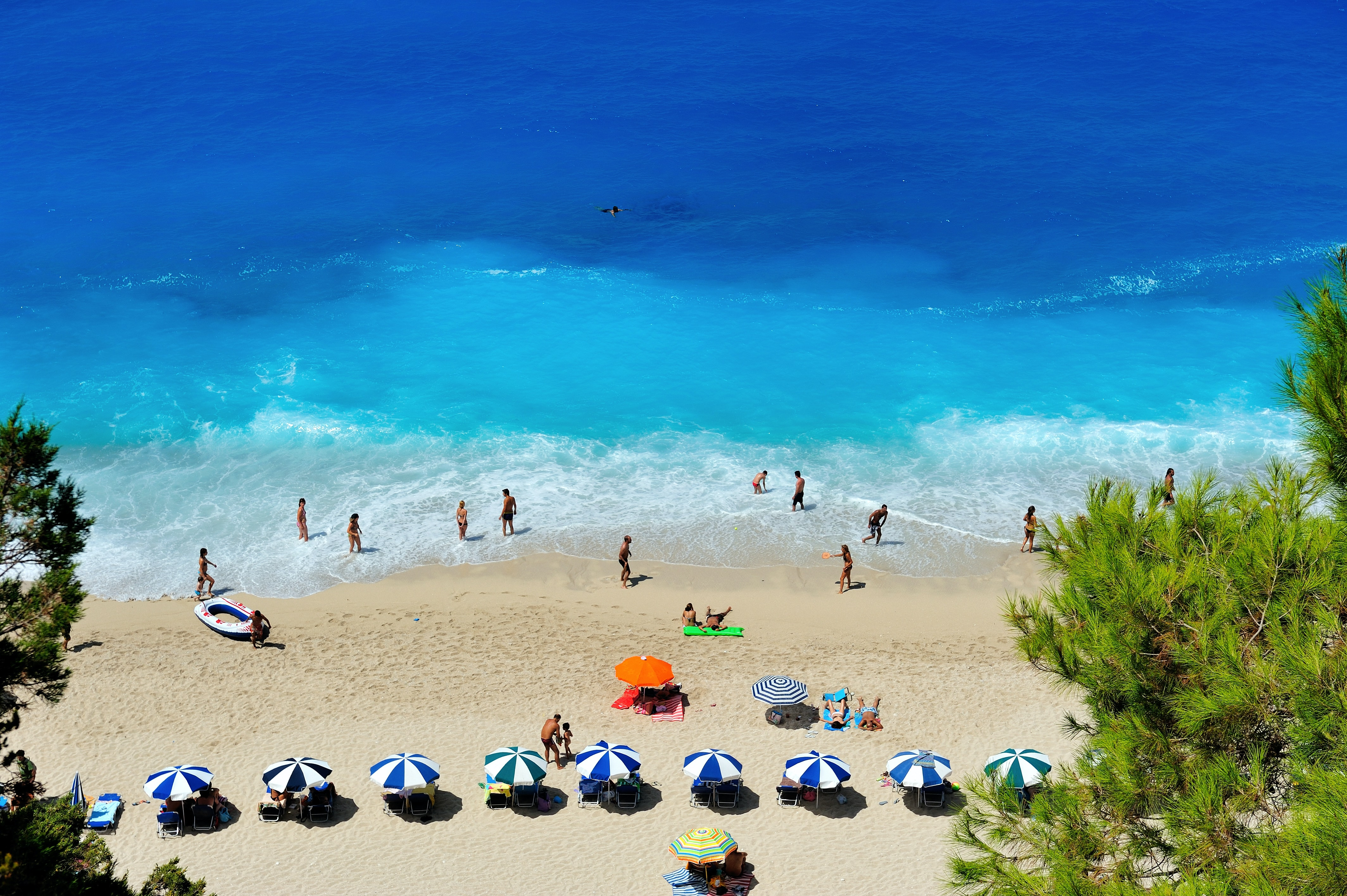 Vacationers reclining on deck chairs and wading through the blue water on a small beach