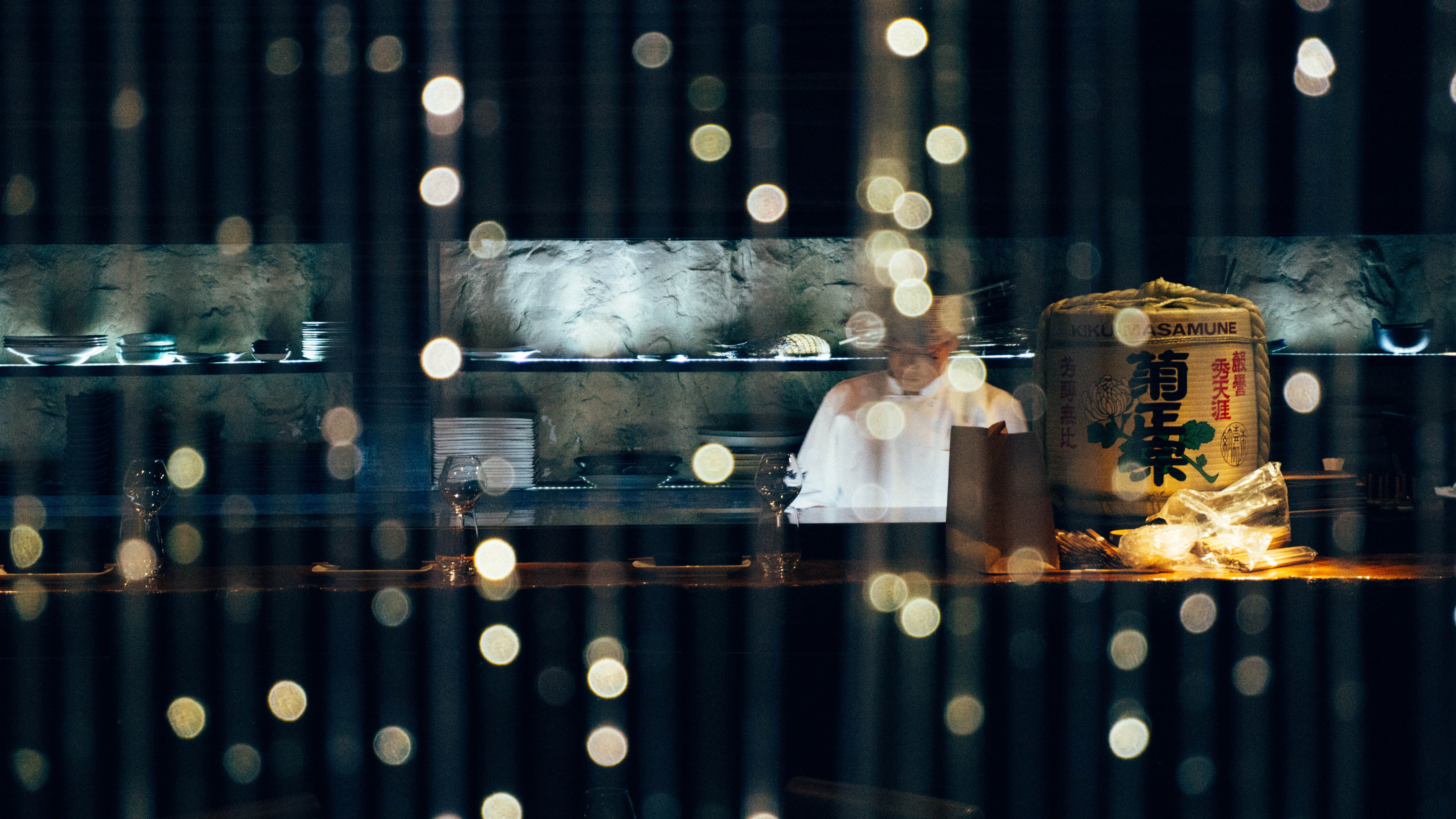 A cook working in an Asian restaurant seen through a window with bokeh effect