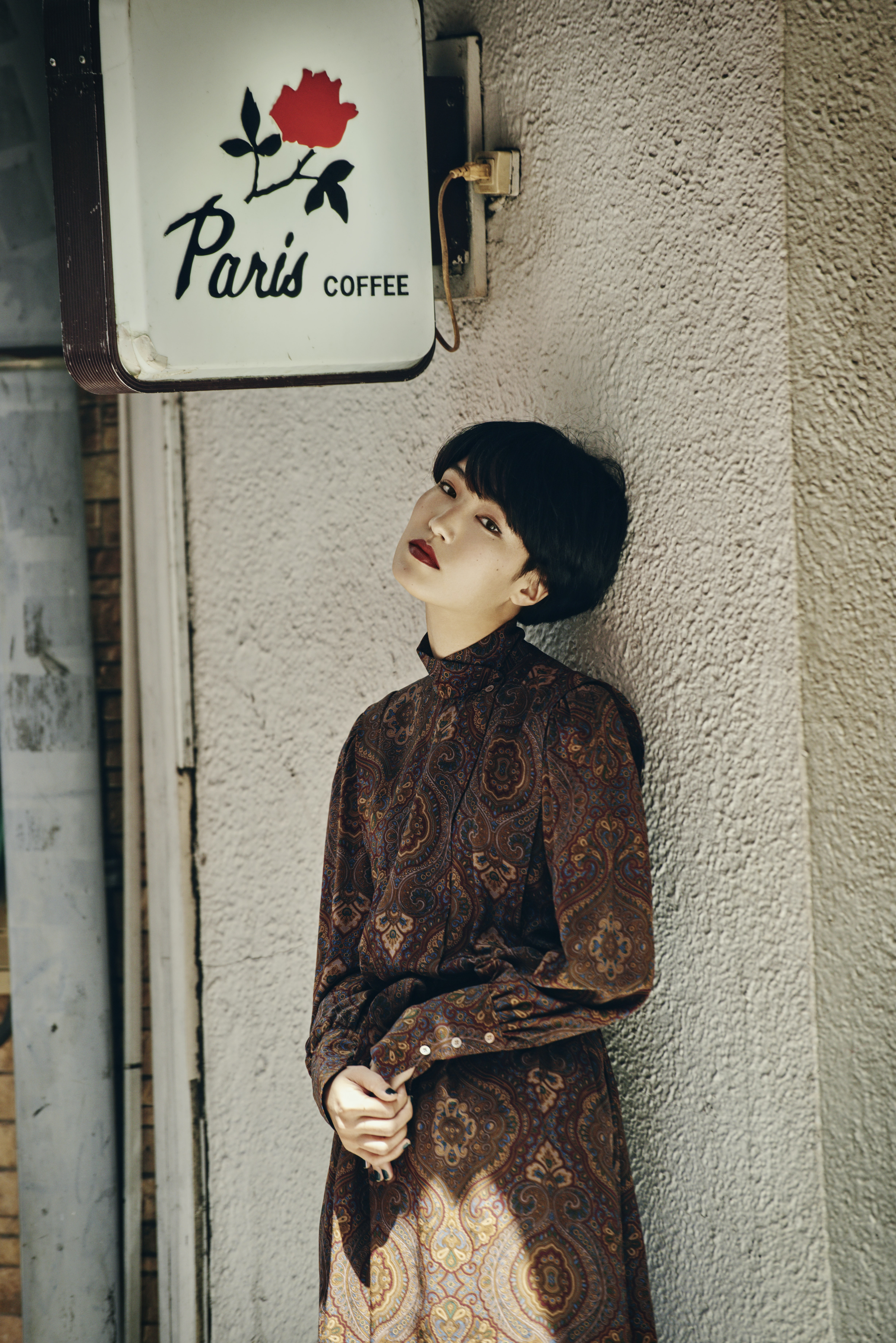 Trendy woman with an edgy haircut leaning against a wall