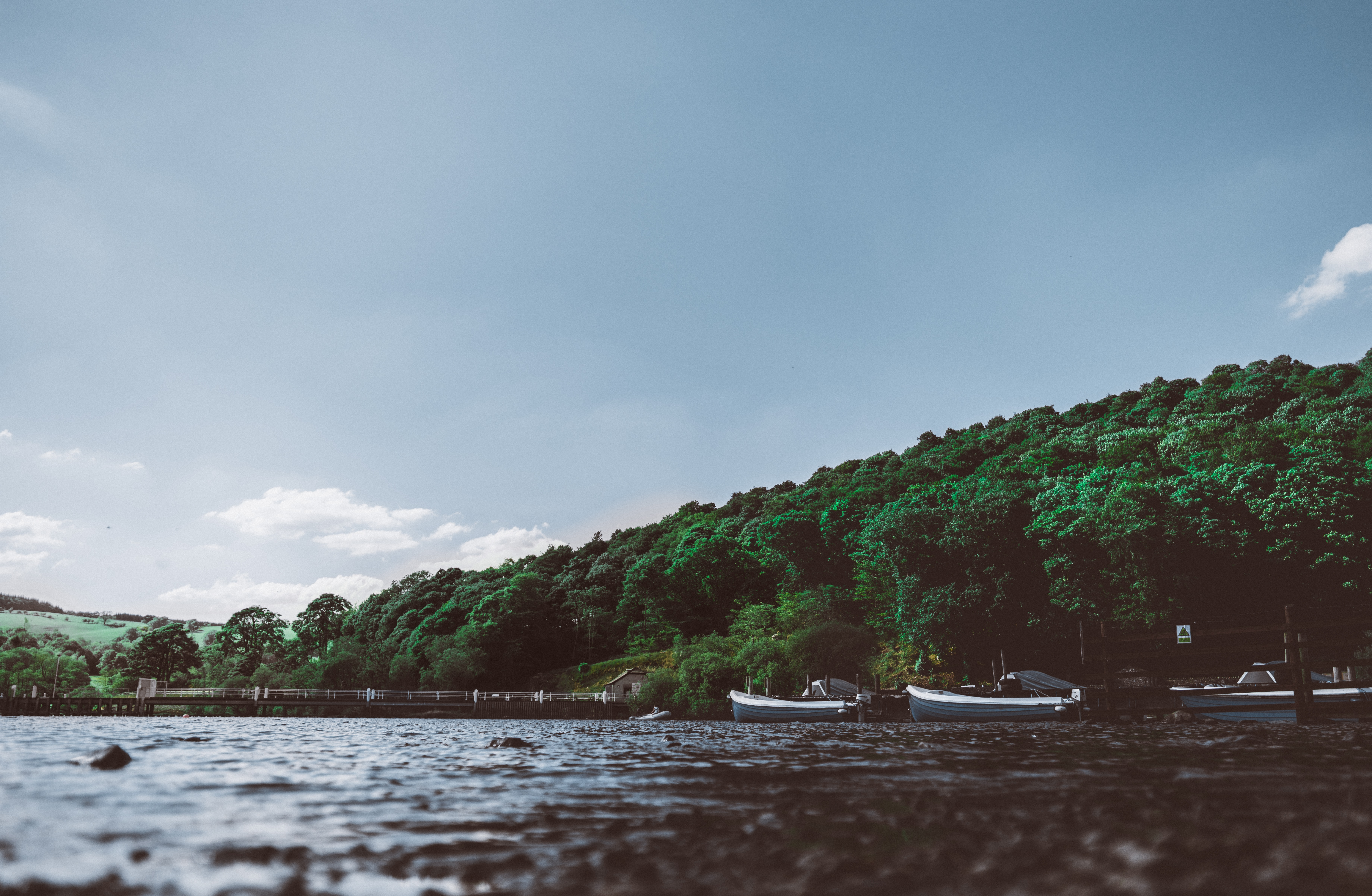 Boats moored at the shore of a choppy lake