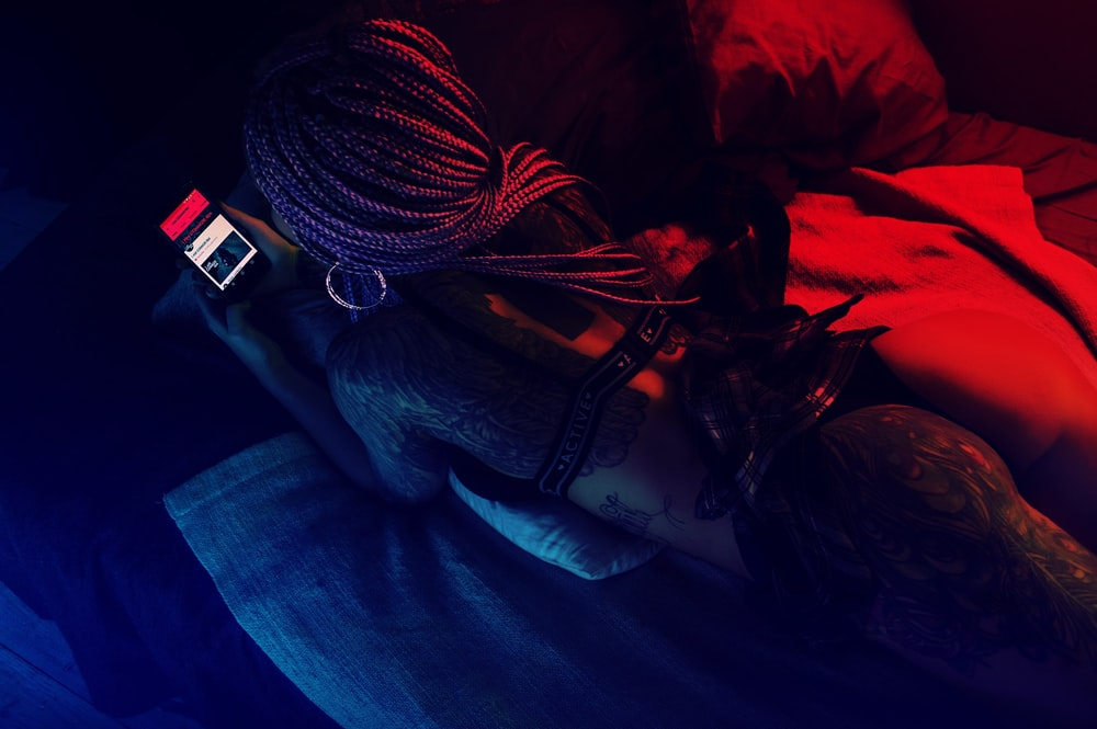 woman lying on bed holding smartphone