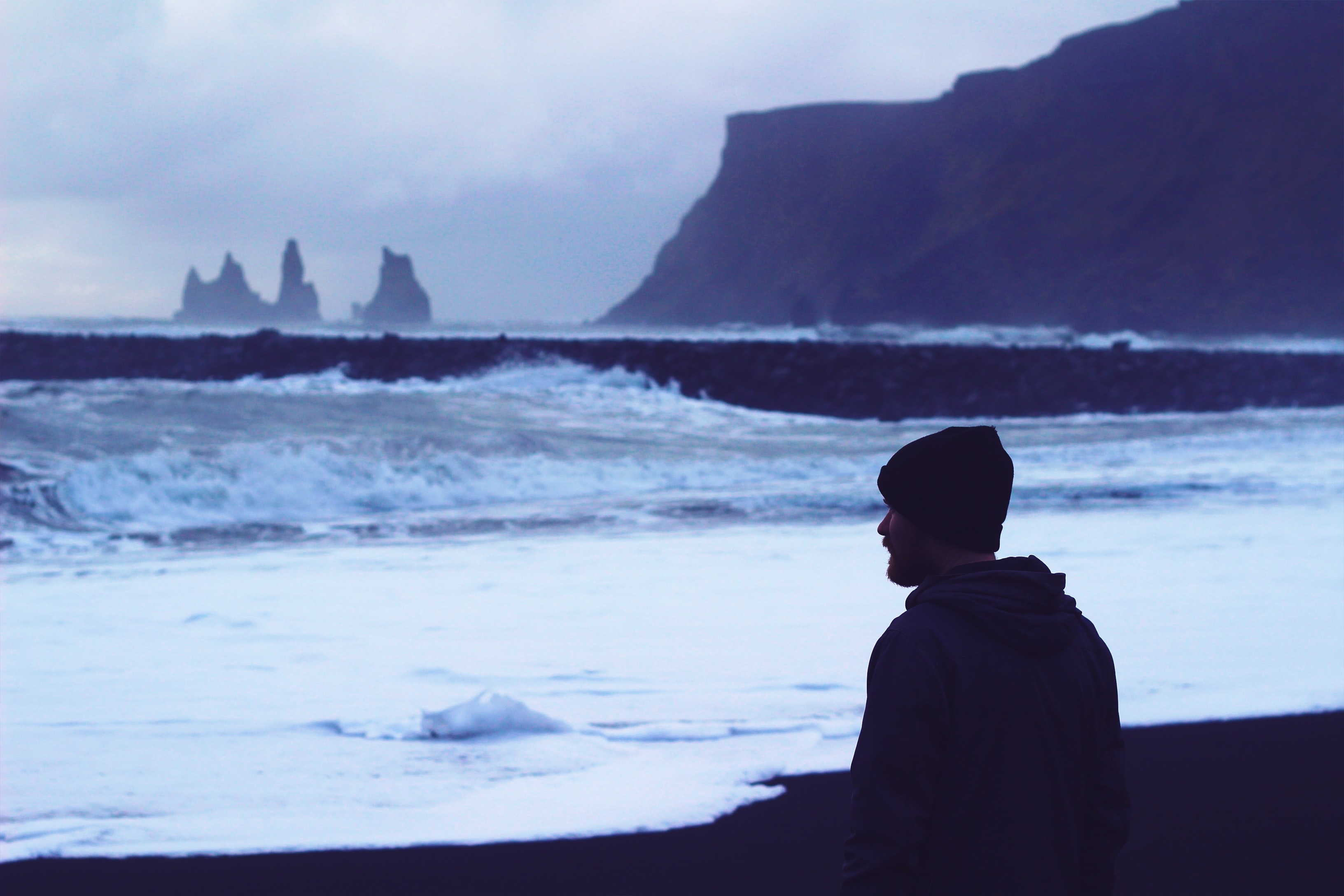 Man in a cap looking at the rough ocean on the rocky coastline at Vik