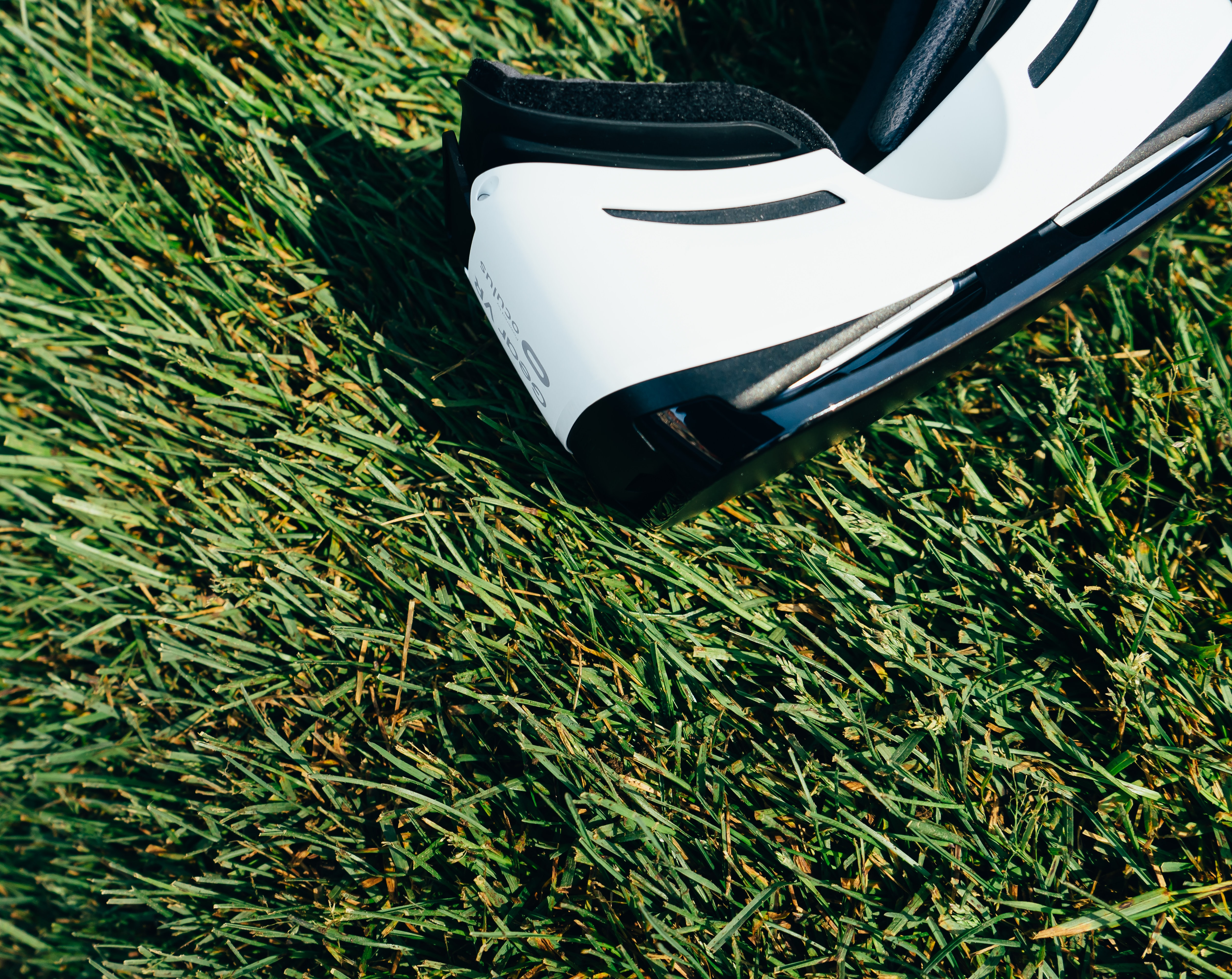 A Gear VR Oculus headset resting on grass during a sunny day