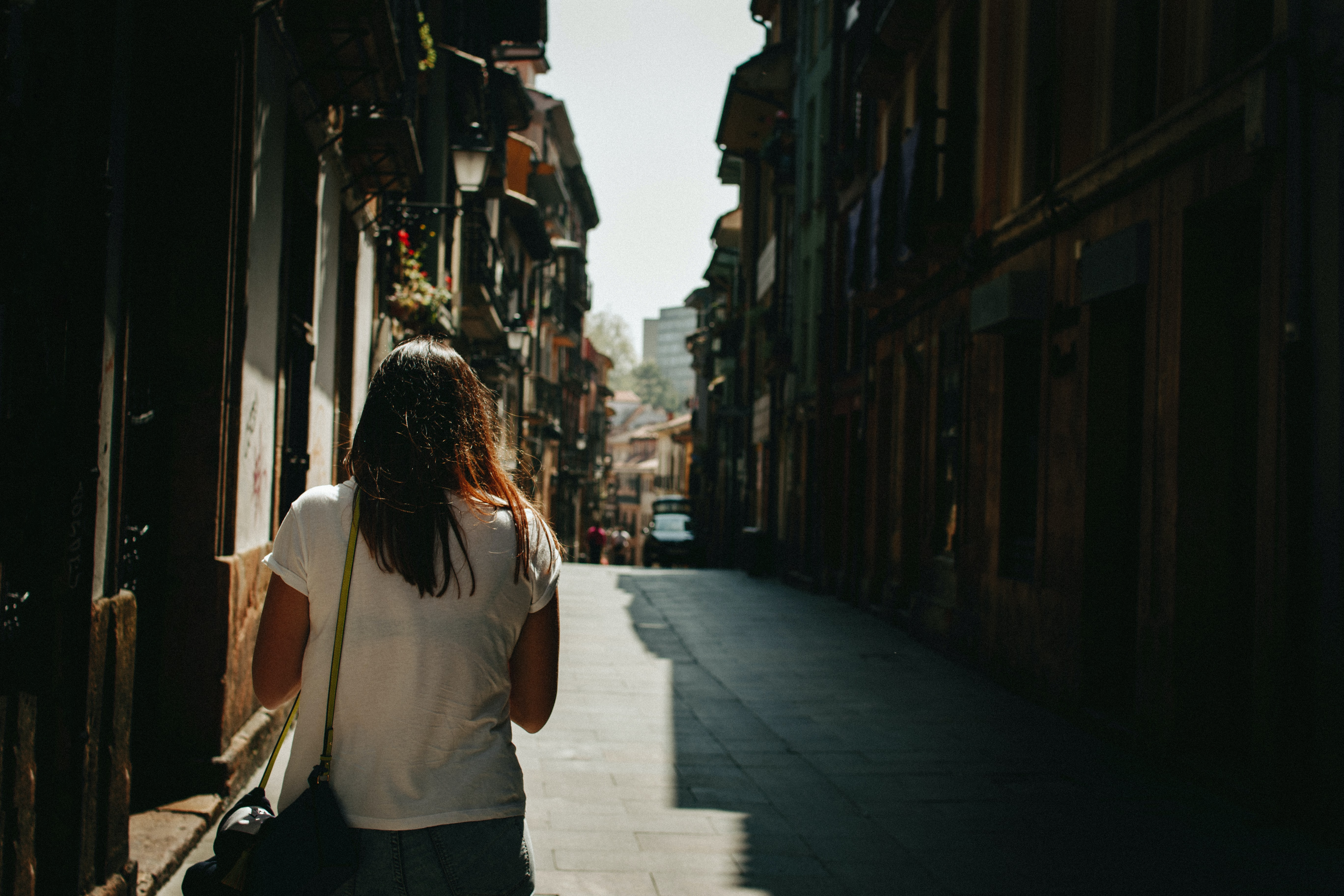 woman waking on pathway between houses