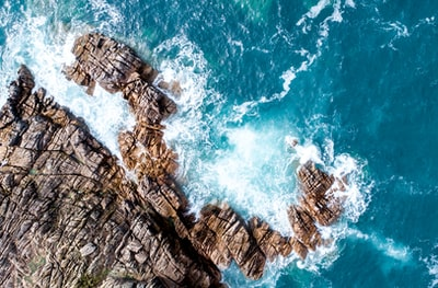 rock mountain next to ocean water drone view teams background