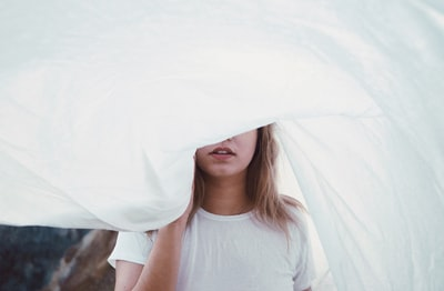 woman under white cloth sheet teams background
