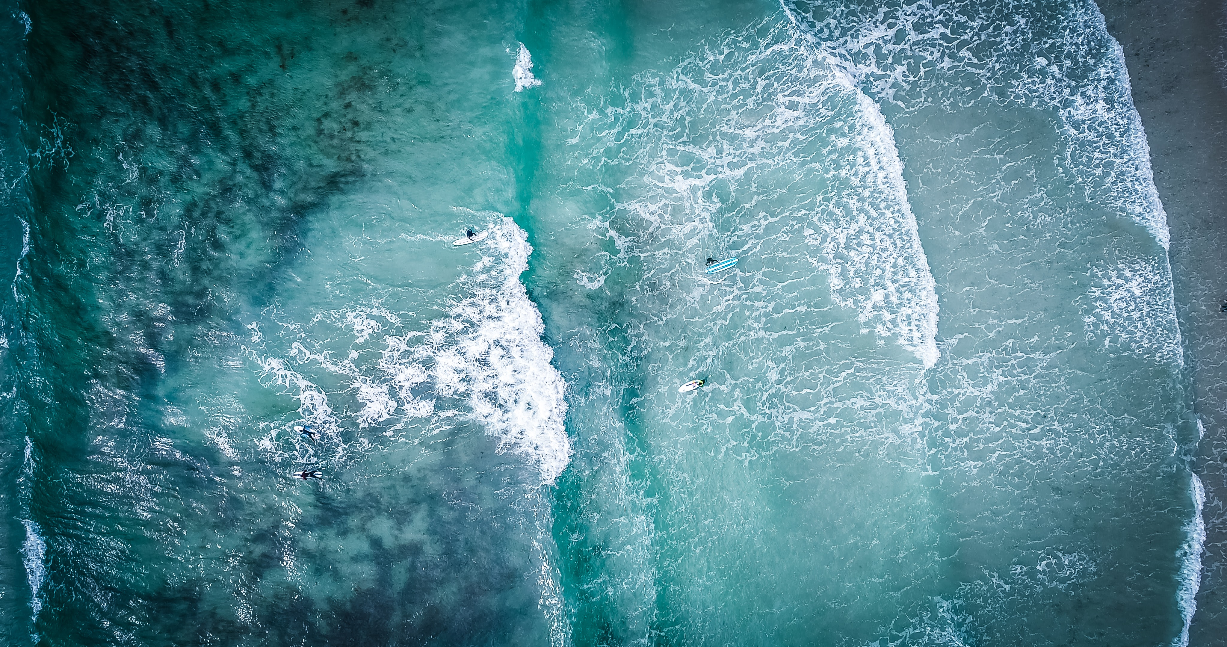 An overhead aerial shot, by drone, of surfers in the foaming sea at Vazon Road