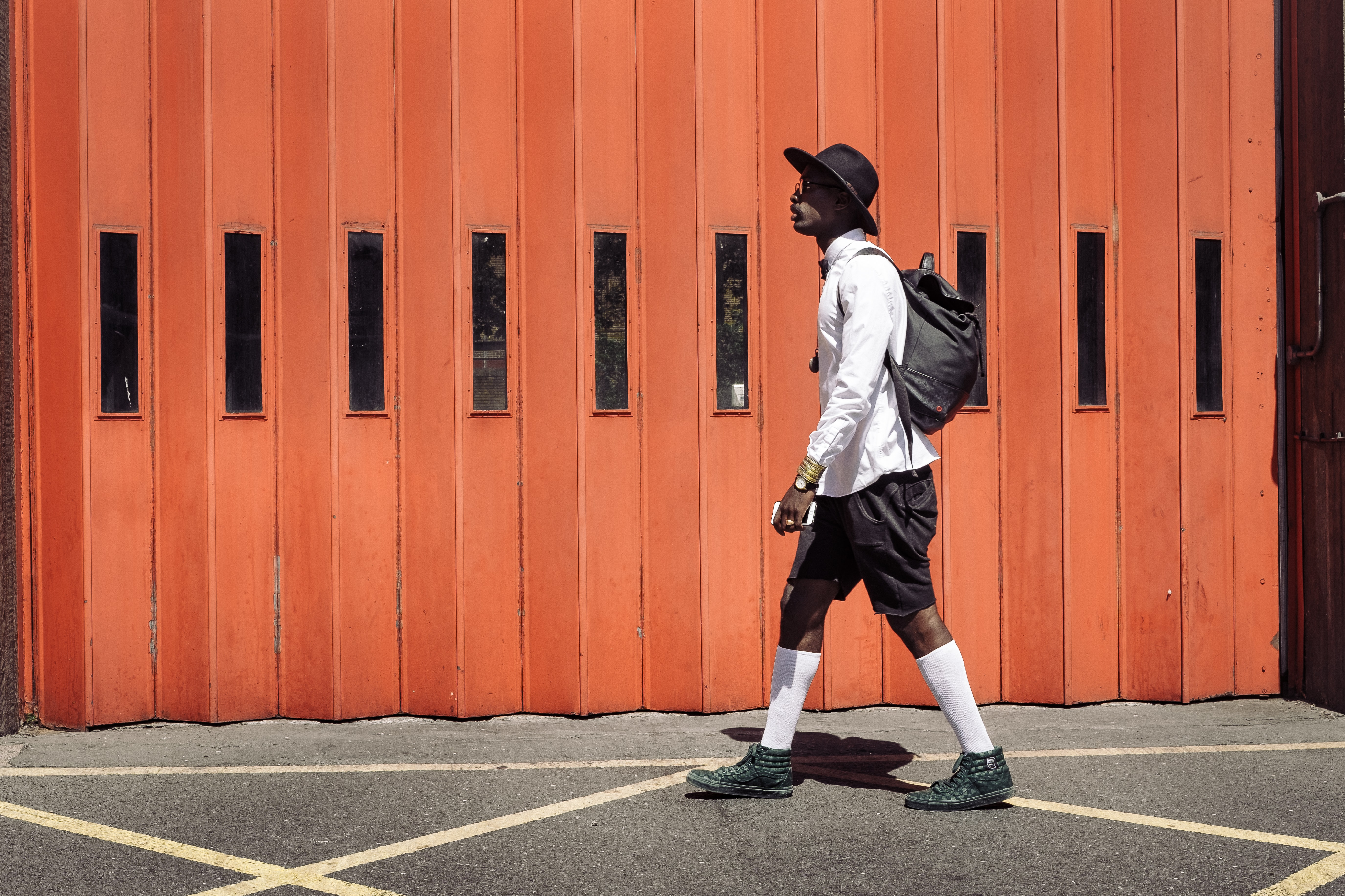 man wearing black hat and white dress shirt walking on street near orange gate