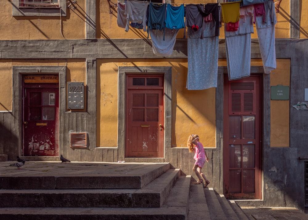 person walking on stairs beside brown door house