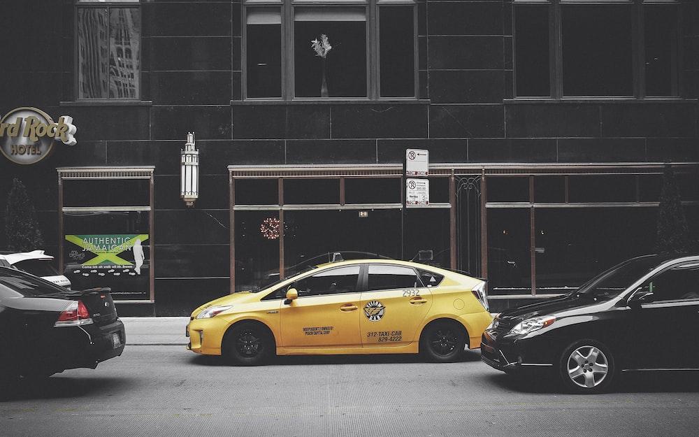 yellow sedan in front of brown building