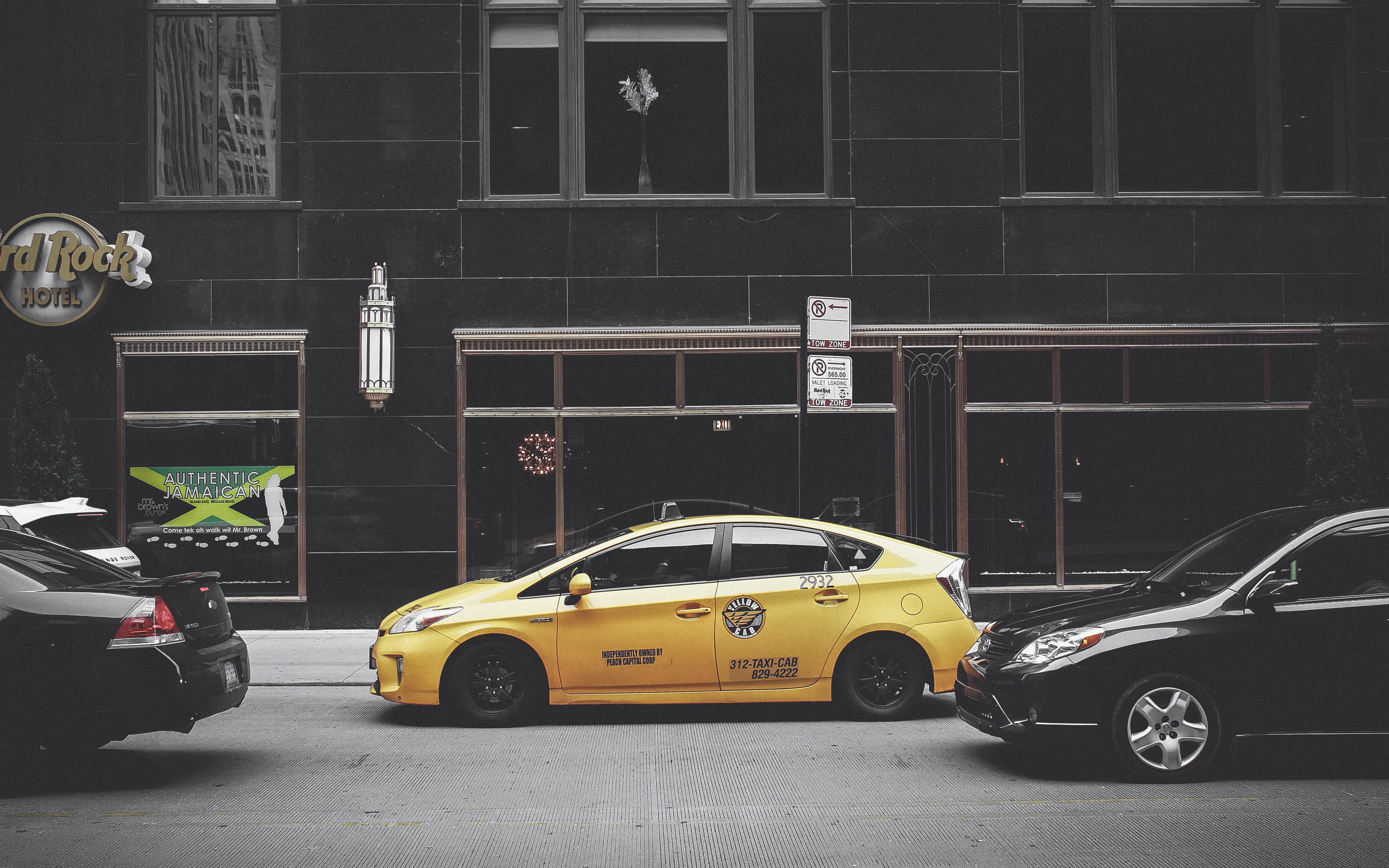 Yellow taxi cab parked on a busy street by a dark building