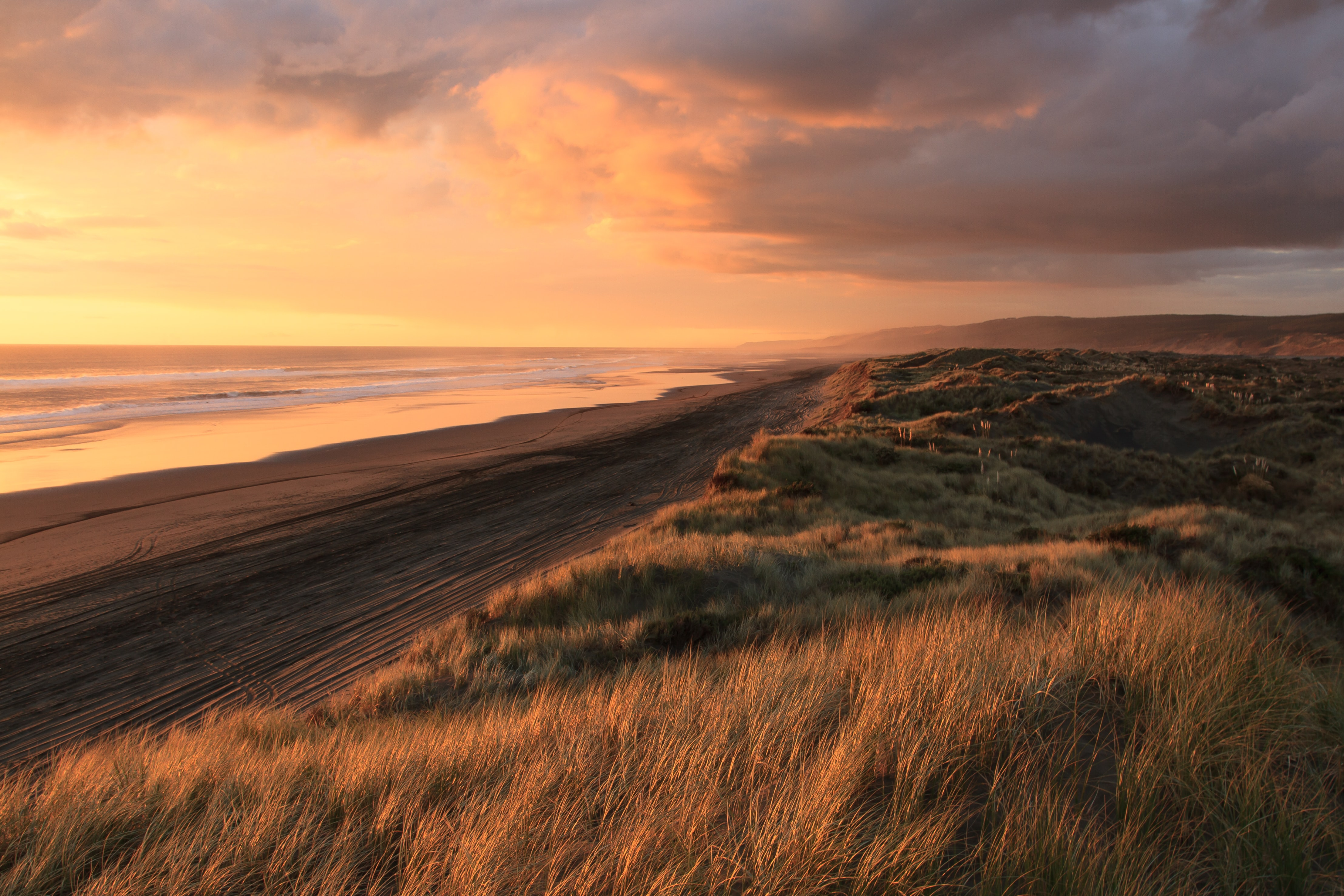 A cloudy sunset over the grassy sand dunes and coastal water at Port Waikato, Tuakau, Auckland, New Zealand