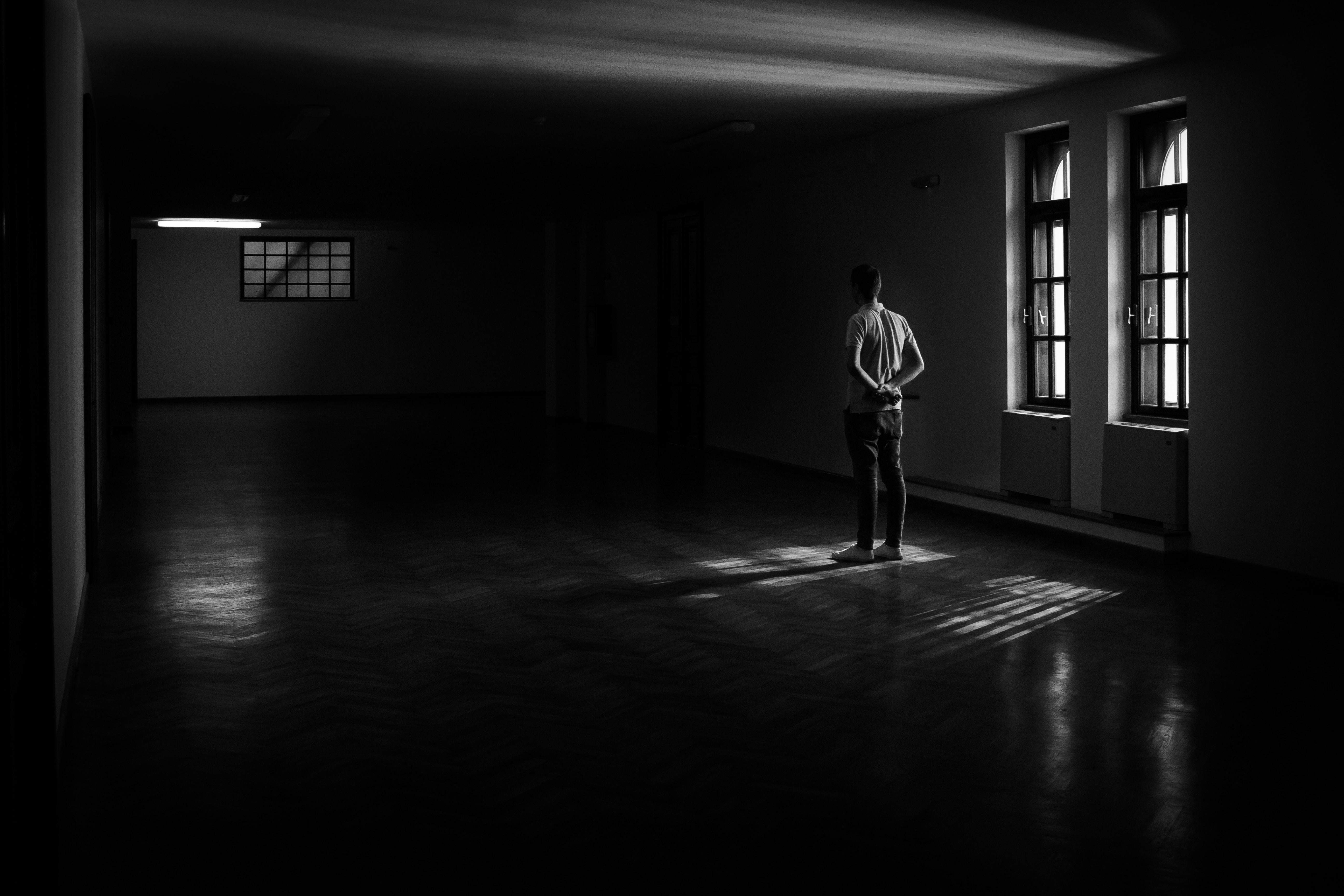 man standing near window inside house