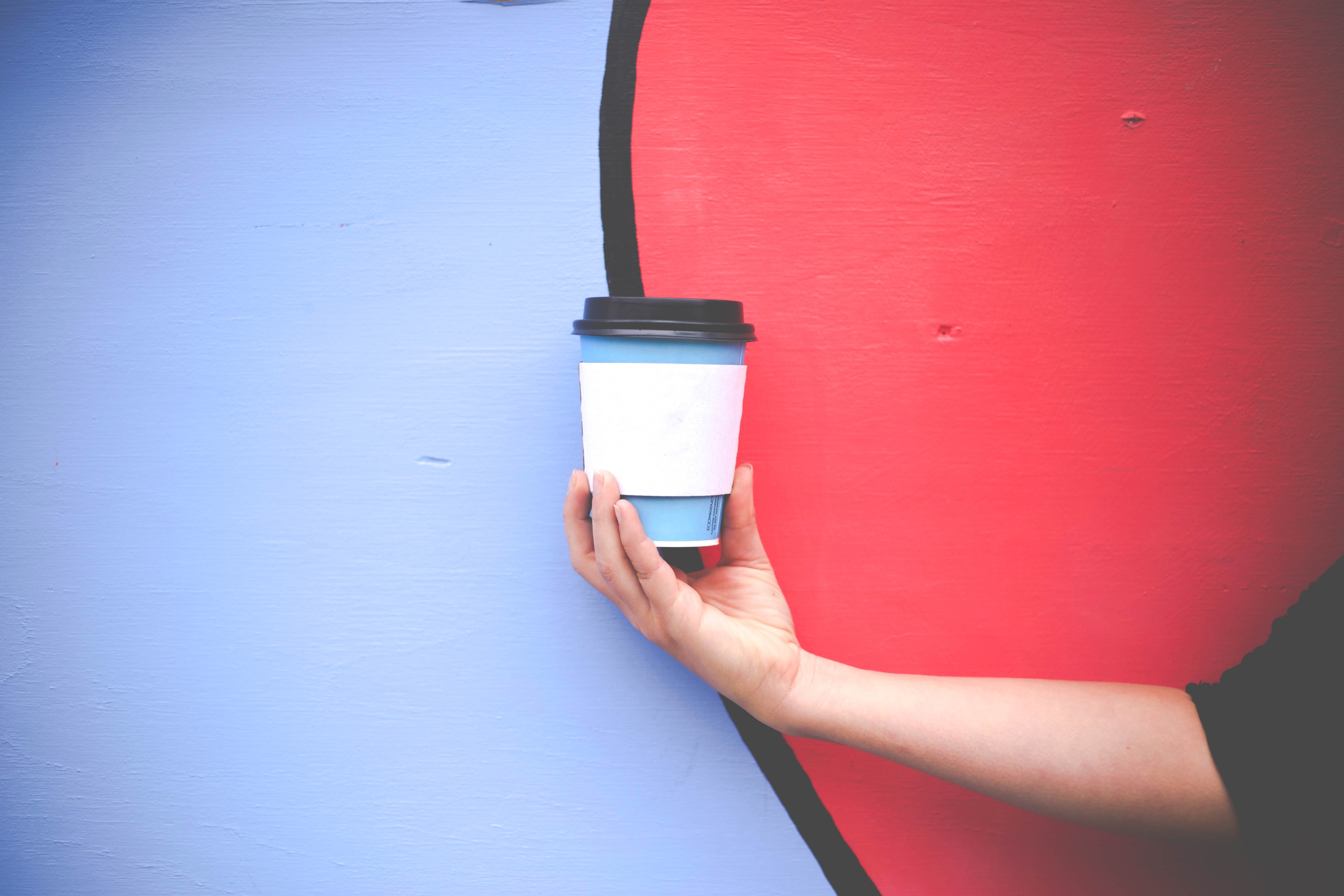 person holding blue and white disposable cup