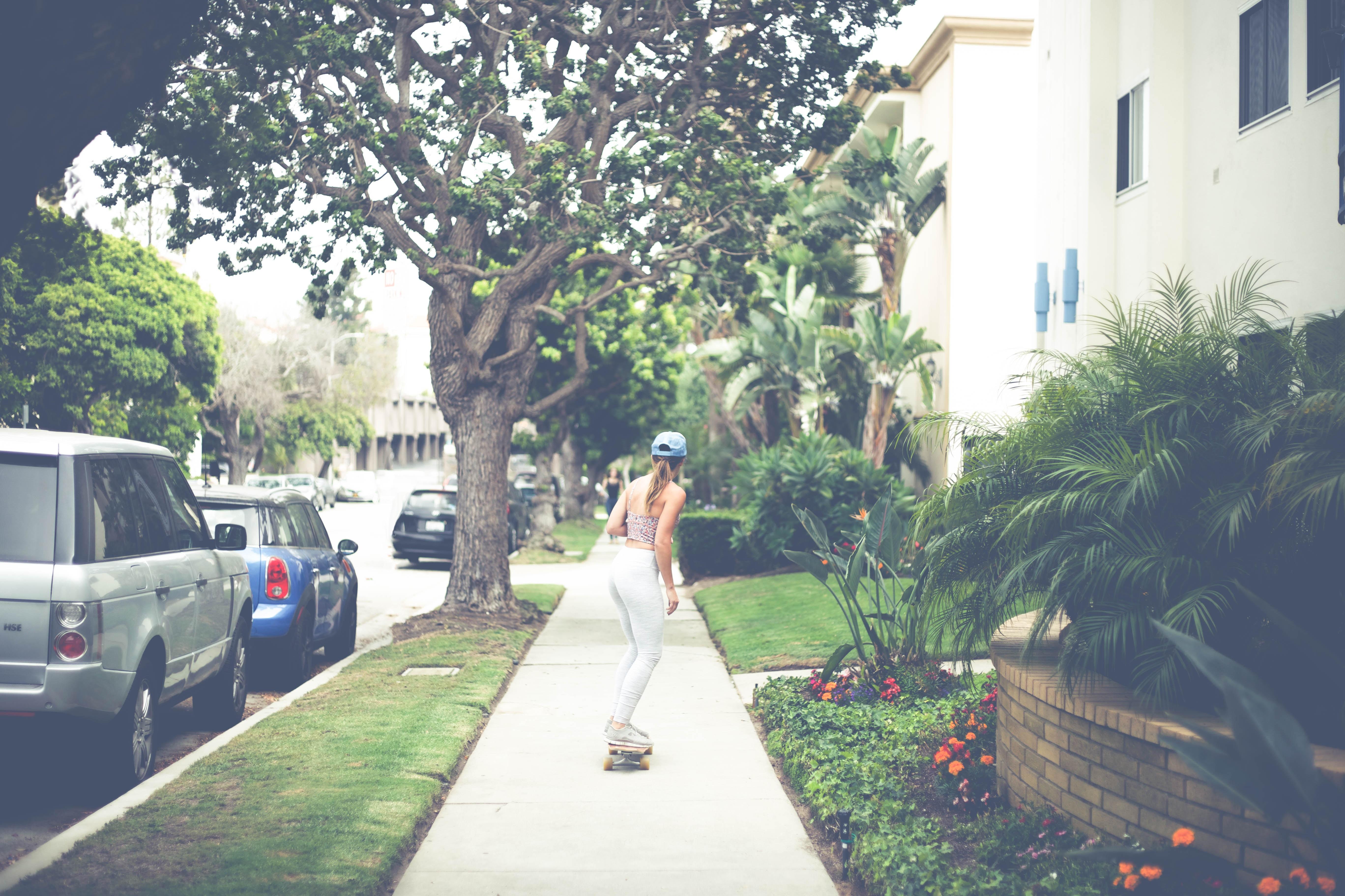 A girl skateboarding down the sidewalk in Playa del Rey