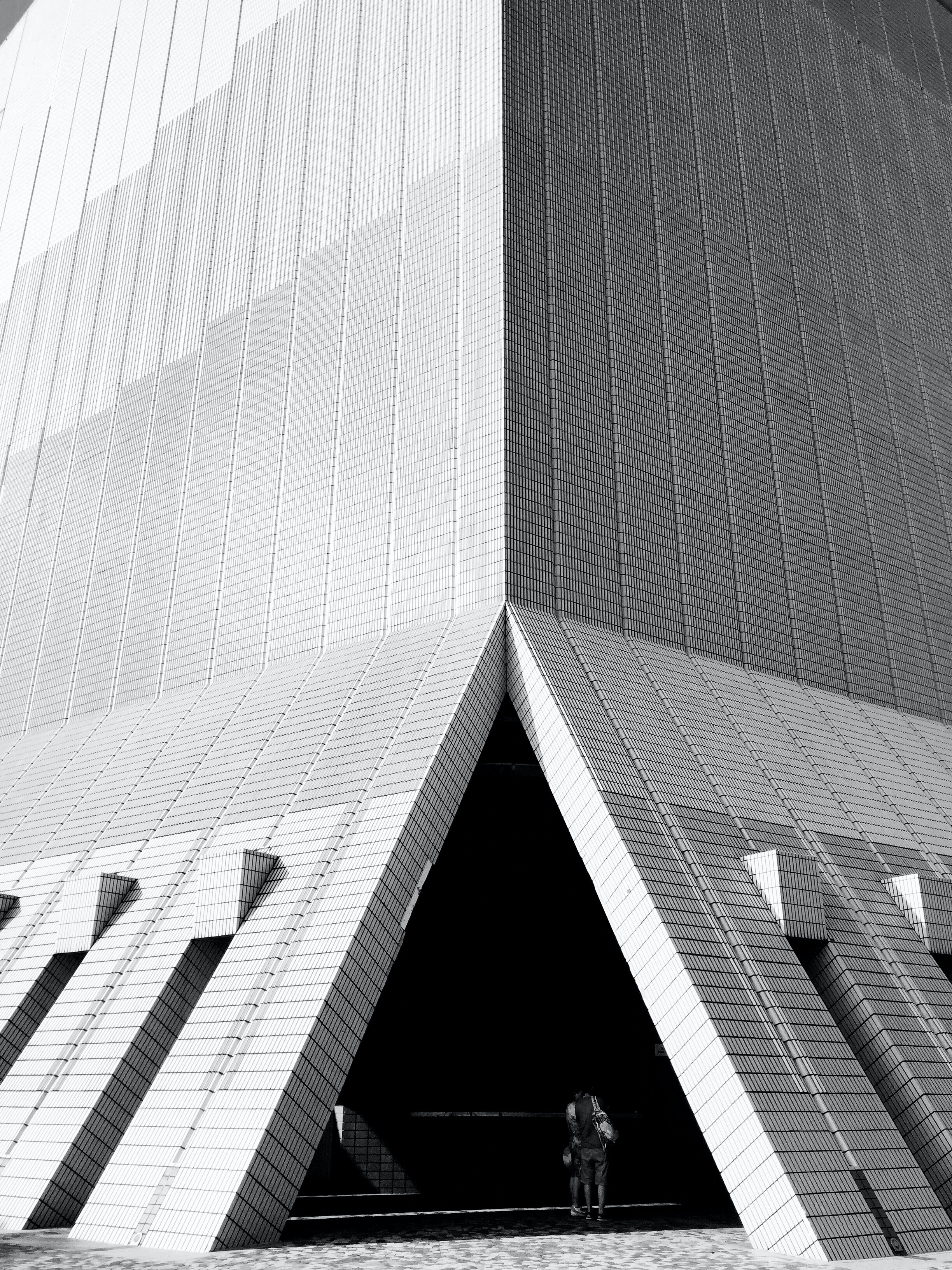 A black-and-white shot of a triangular opening at the bottom of a modern building facade