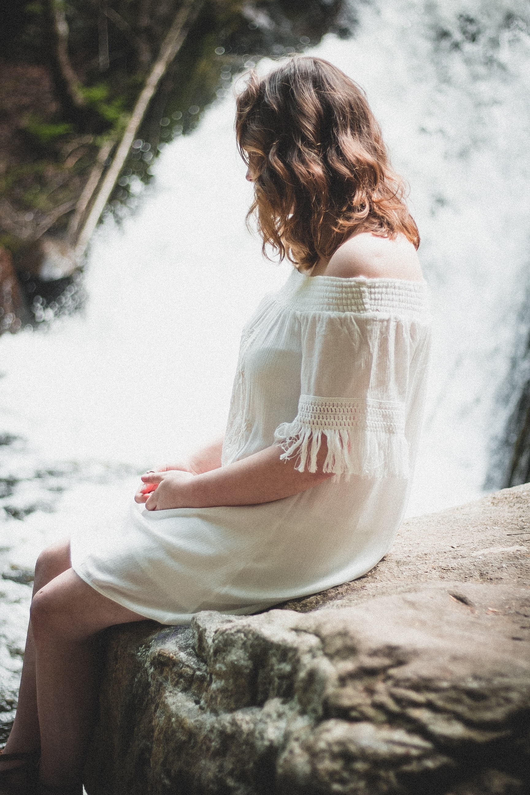 woman sitting on rock beside waterfall at daytime