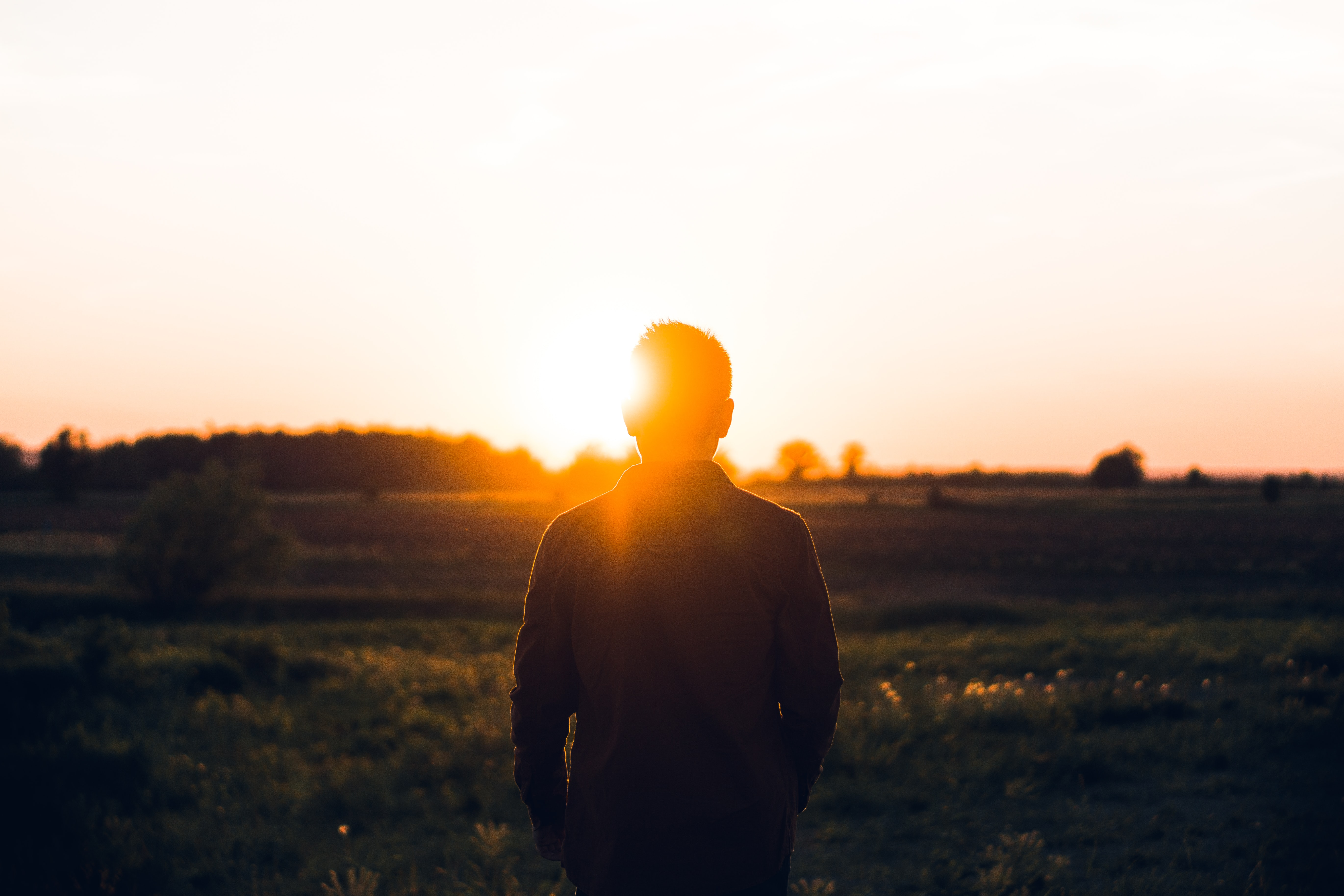 Back of a man's head and body, with the sun flaring right above his left ear, in a field at sunset