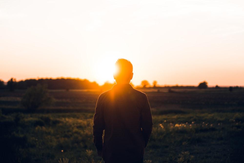 silhouette of man facing sunset