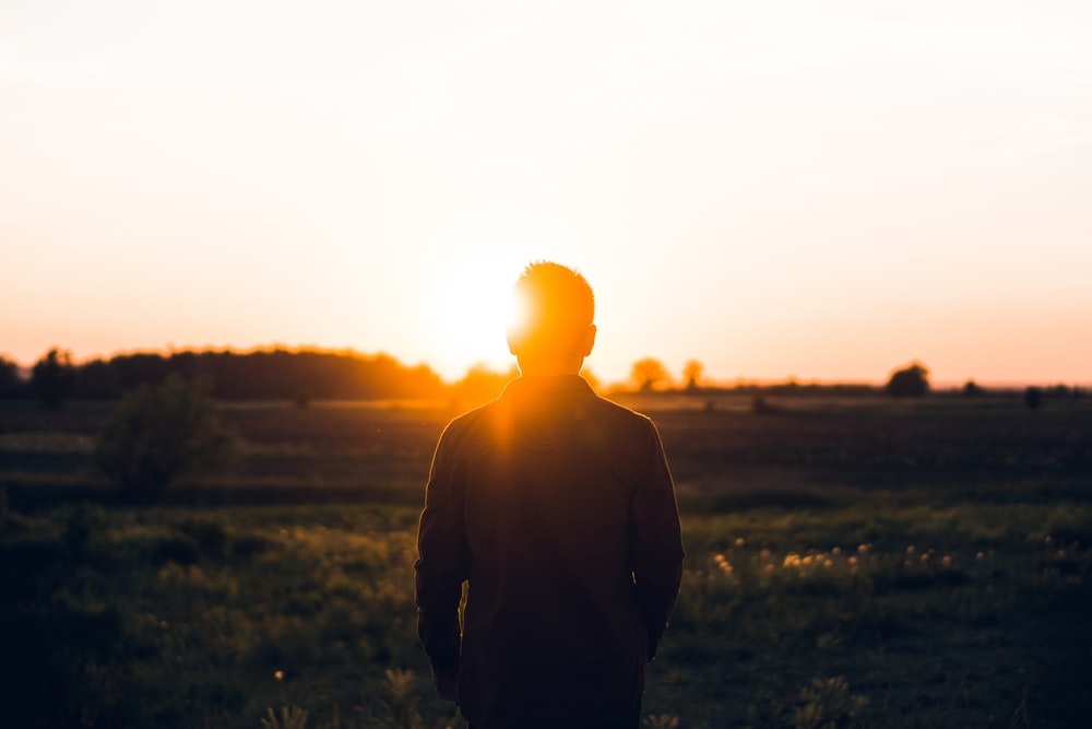 silhouette of man facing sunset