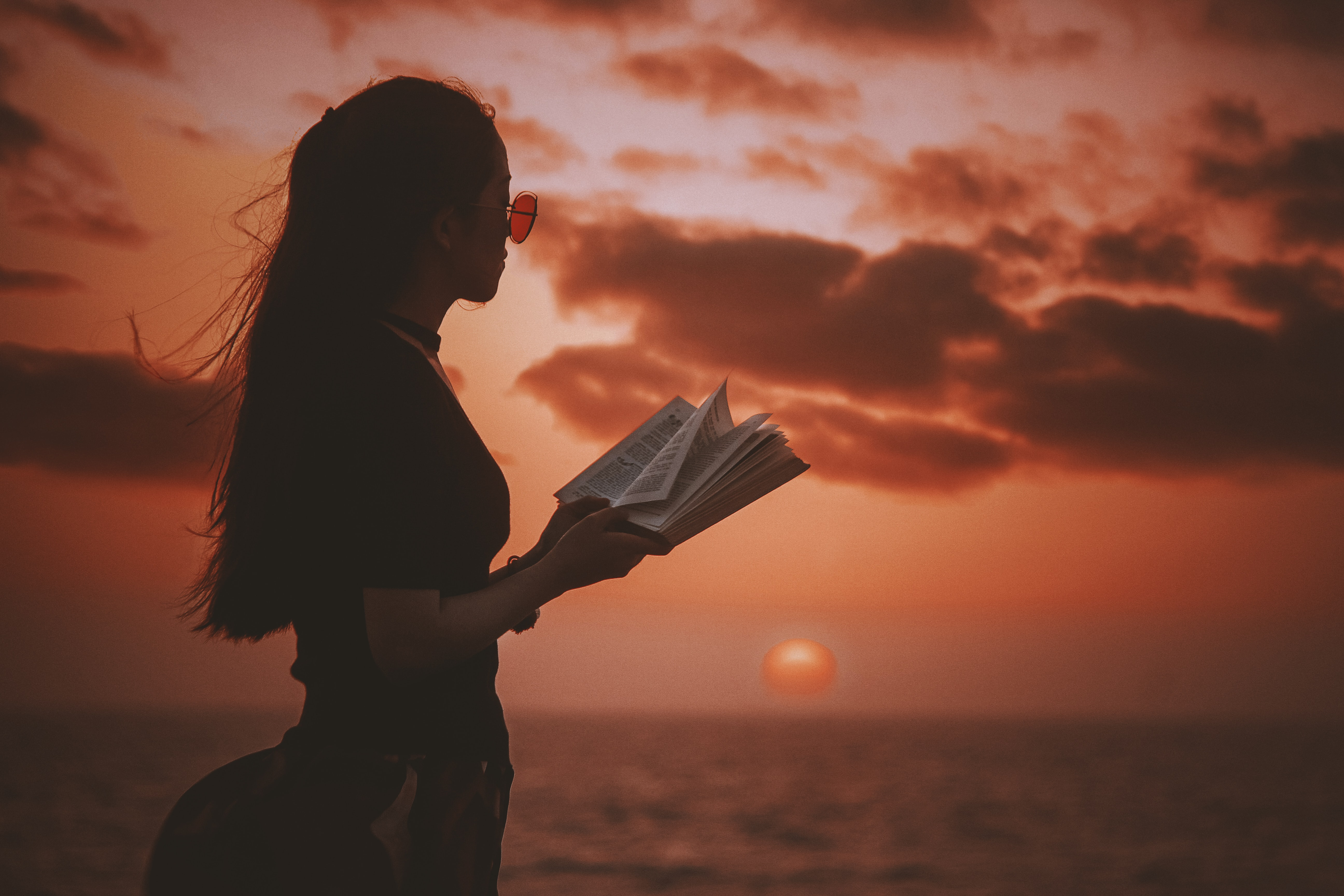 Woman with sunglasses holding book with a sunrise over ocean as the backdrop