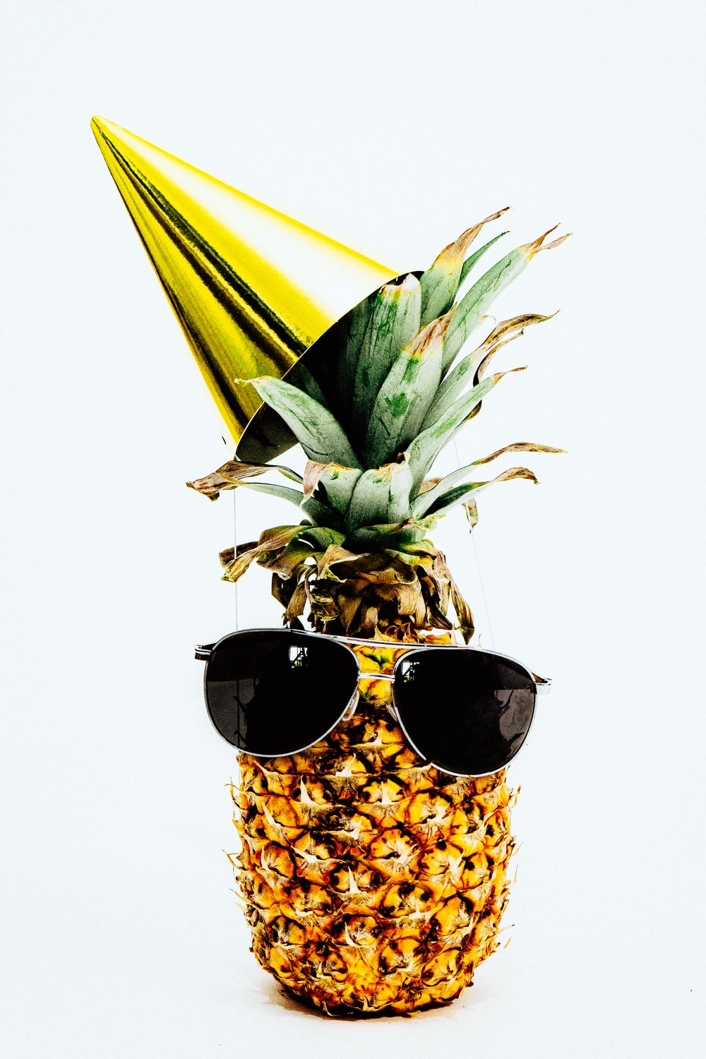 ripe pineapple with yellow cone and sunglasses