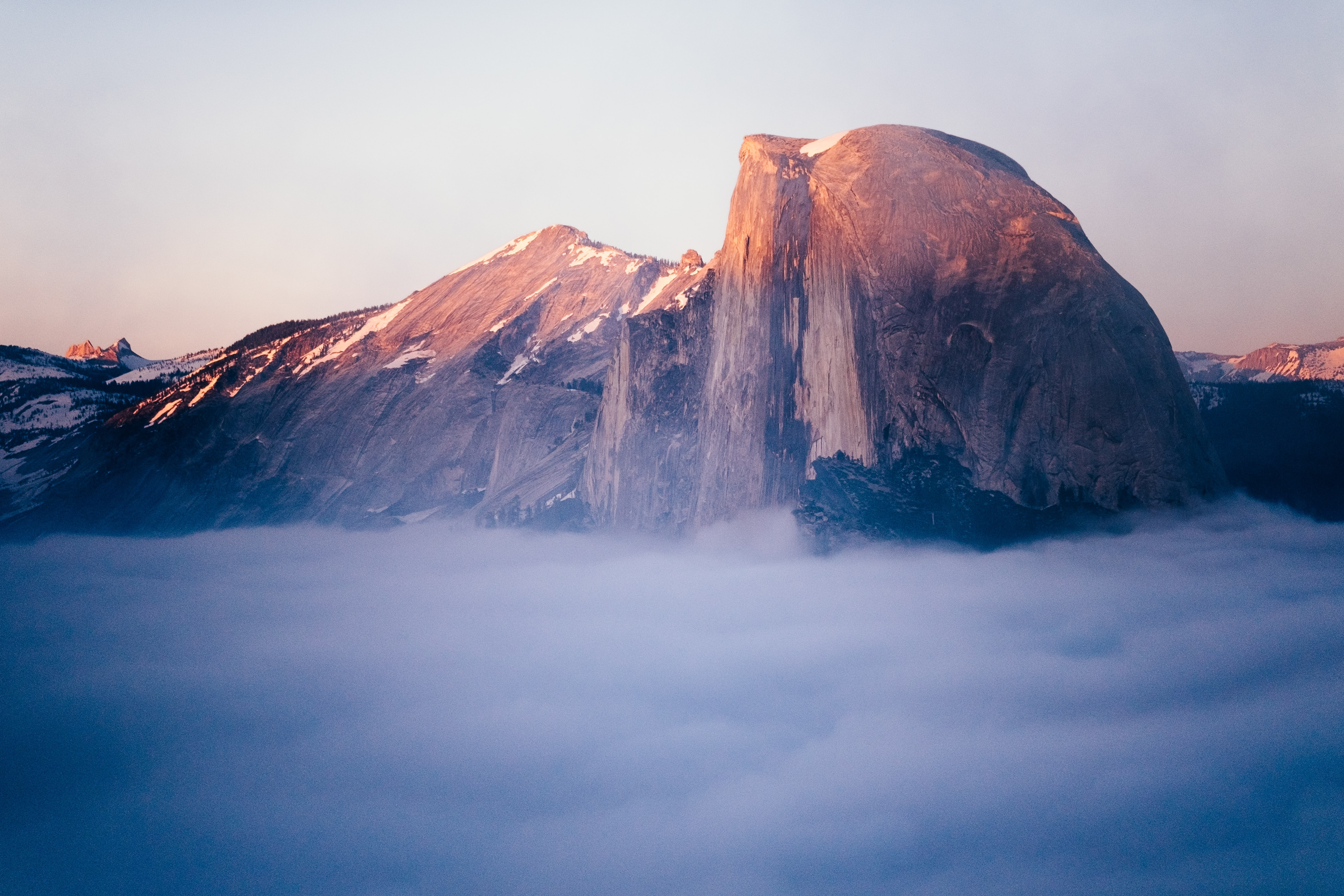 Fog covers the ground of rocky mountain cliffs Yosemite