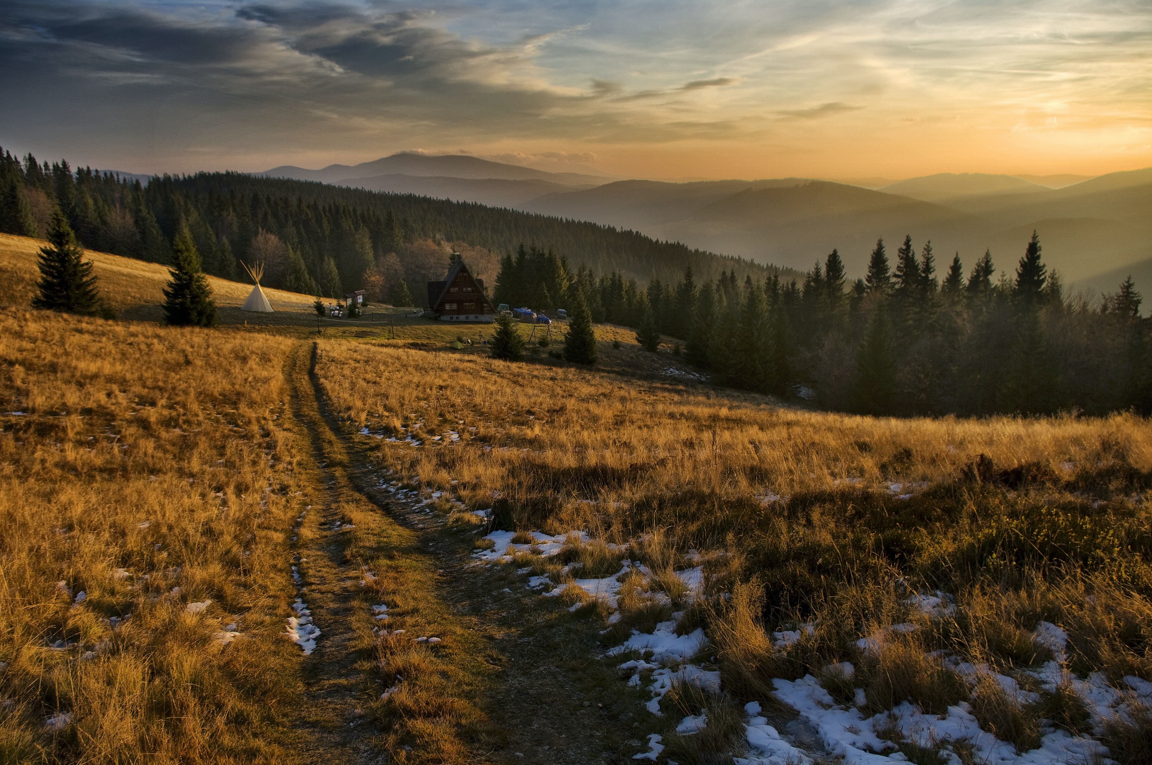 Sunset on a mountain in Bacówka with trees and fields.
