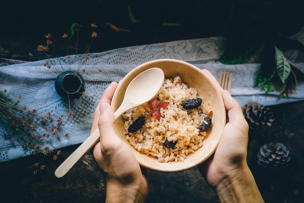 person holding bowl filled with food