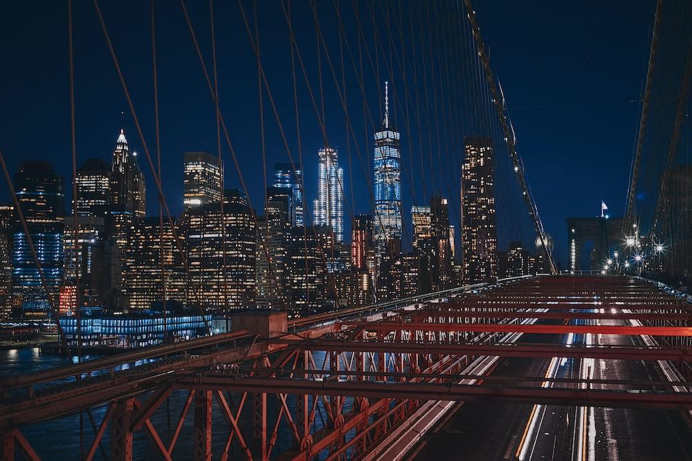 bridge near city buildings during nighttime