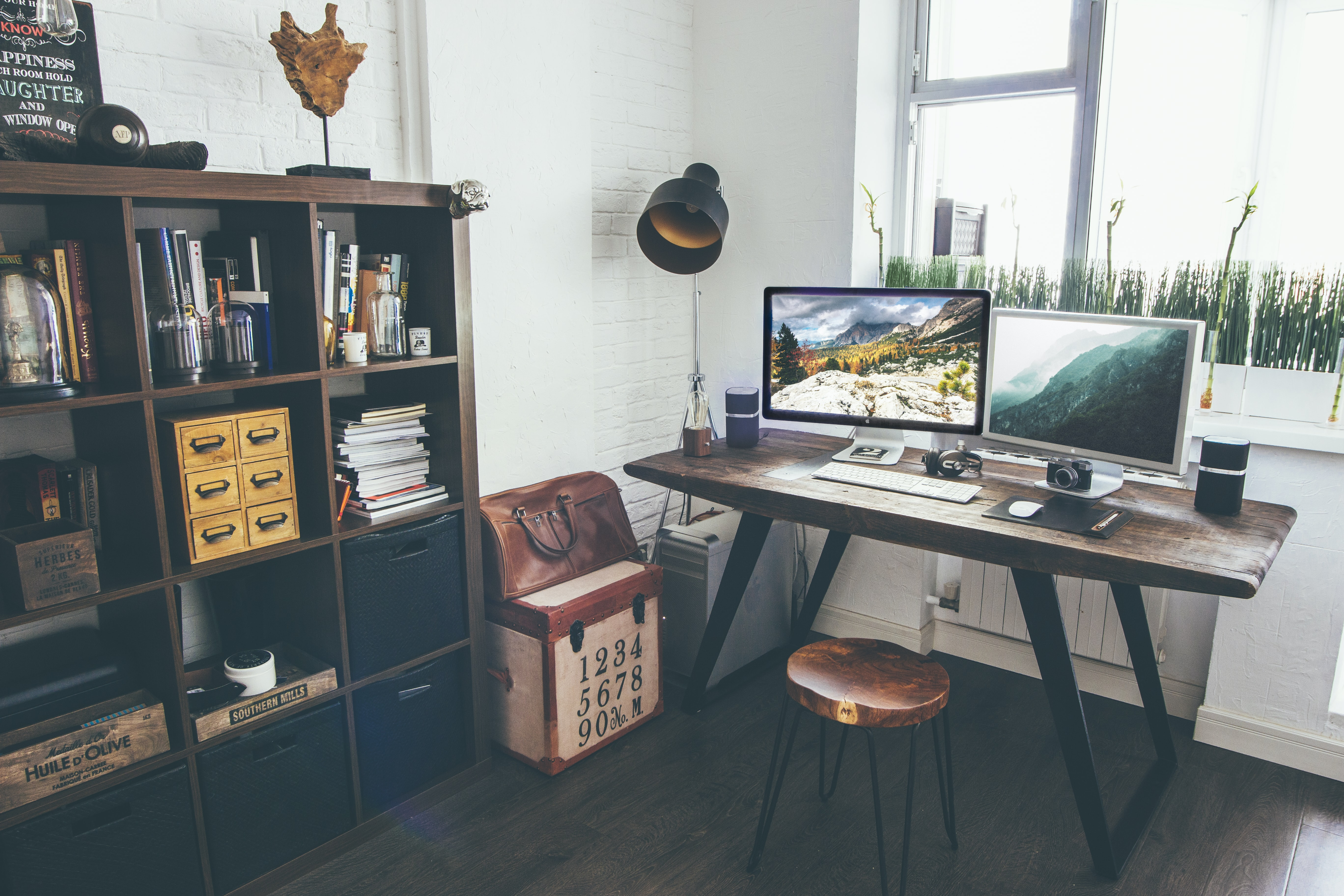 Two iMacs on a desk in a vintage-style home office