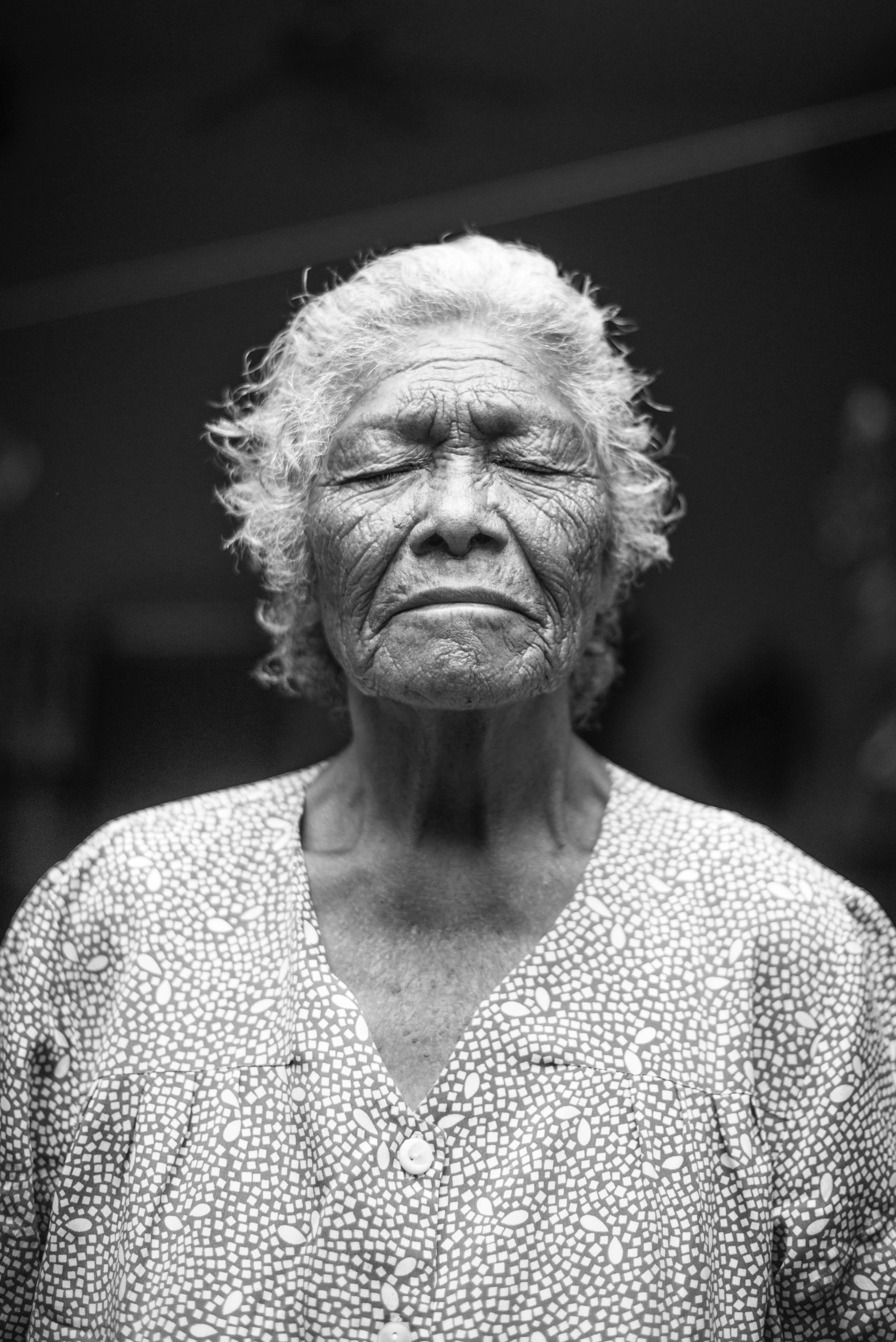 Old grandmother with gray hair and a wrinkled face closing her eyes in black and white.