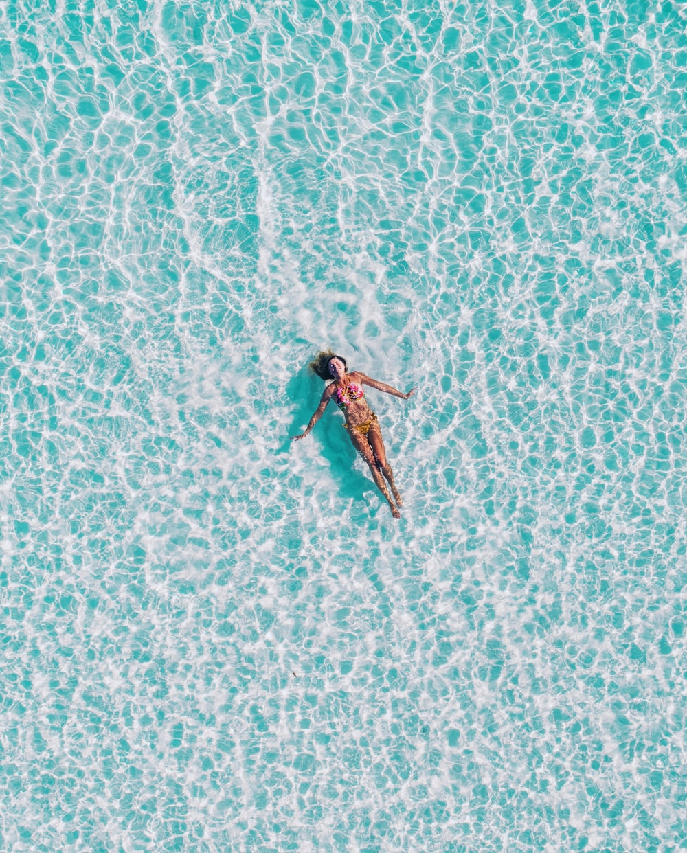 A top view of a woman in a bikini swimming on her back in clear ocean water