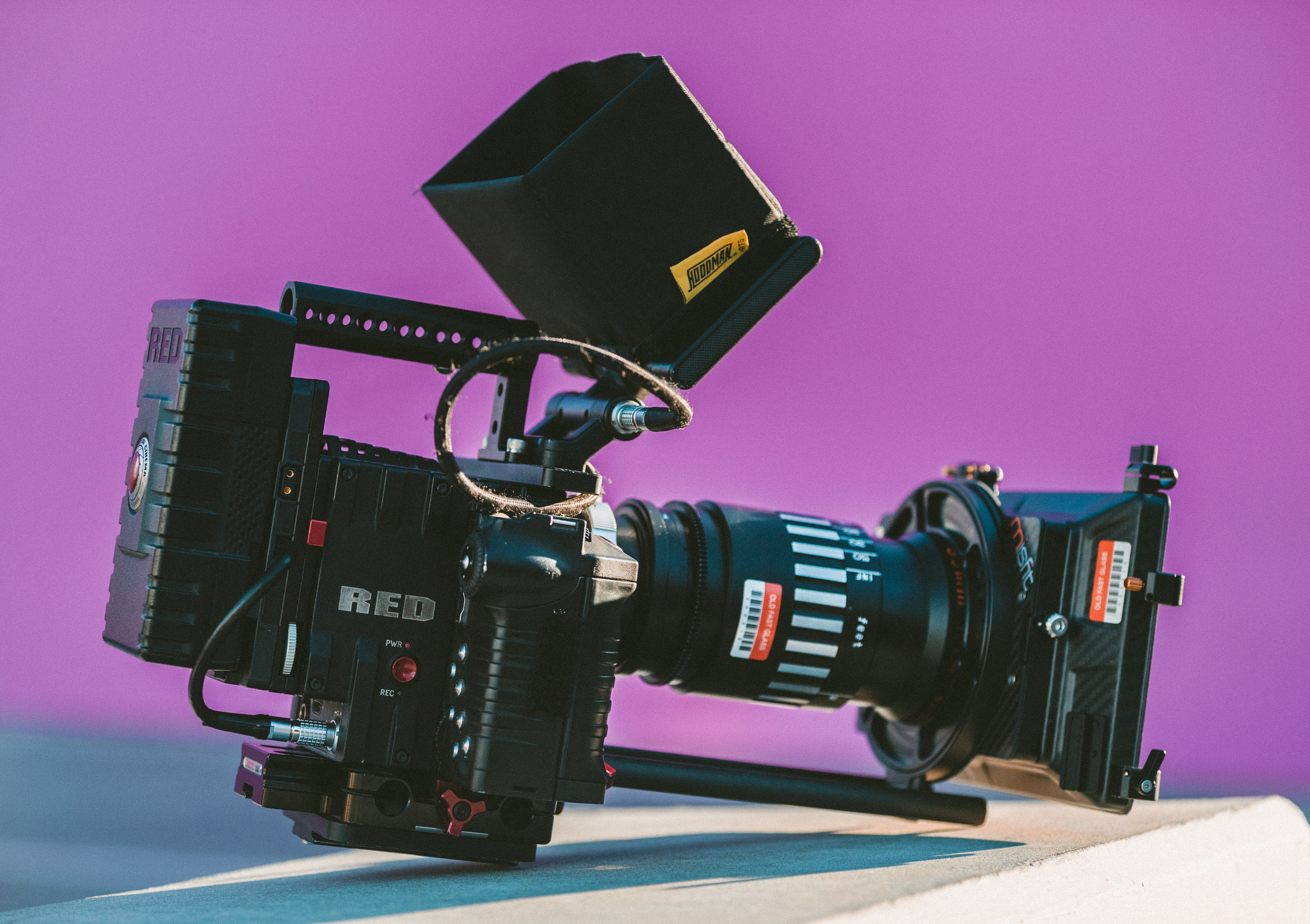 Filmmaking camera with long lens and technology sitting on surface in front of purple background