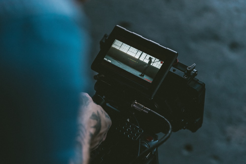 person holding black shoulder-mount video camera