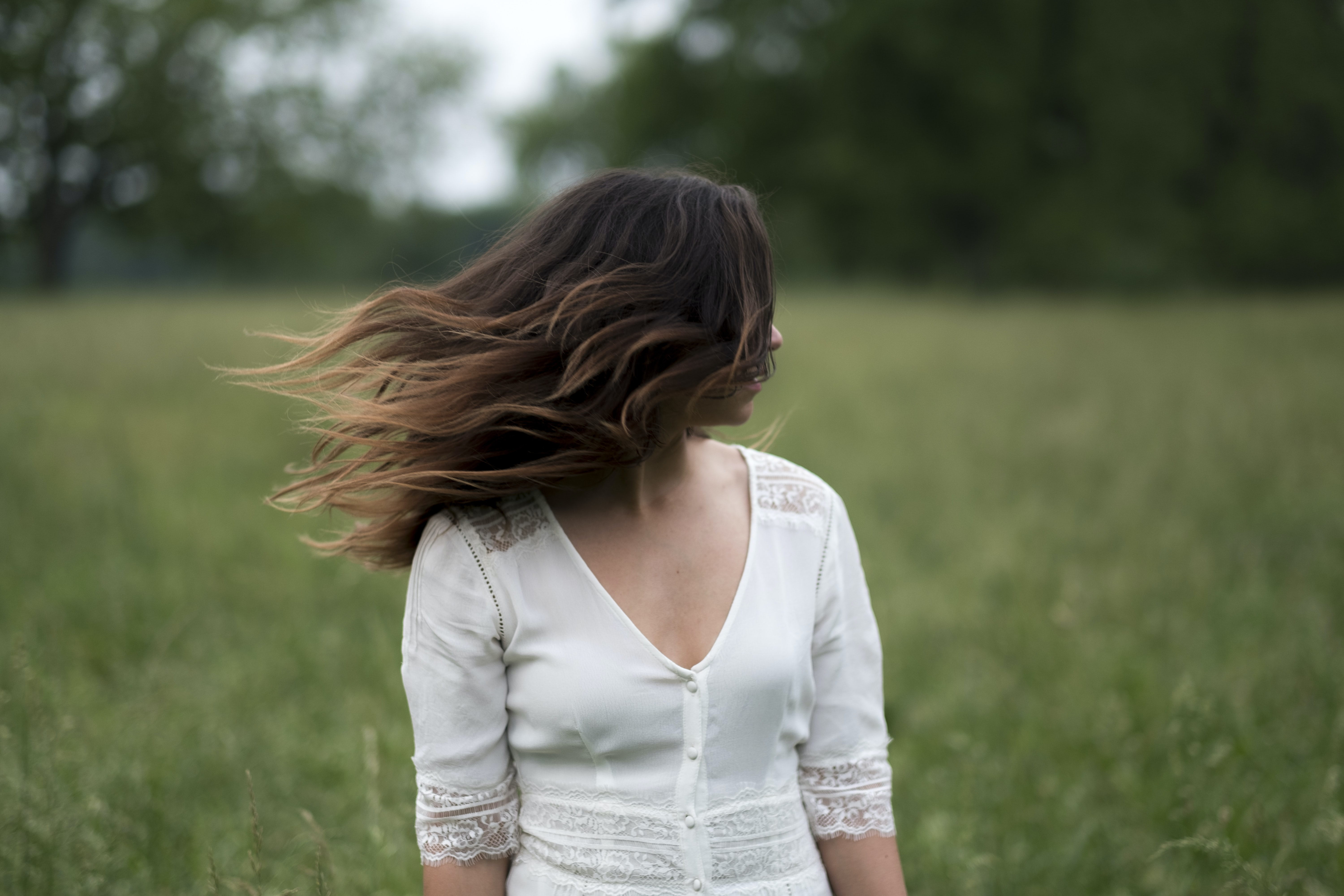 Woman in a white shirt with windblown hair in a field