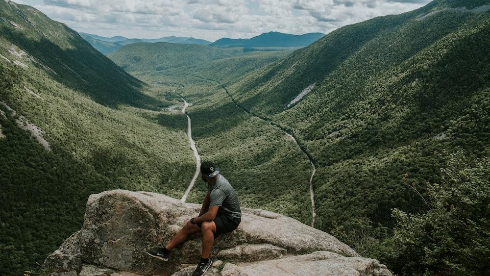 man sitting on rock looking at mountain