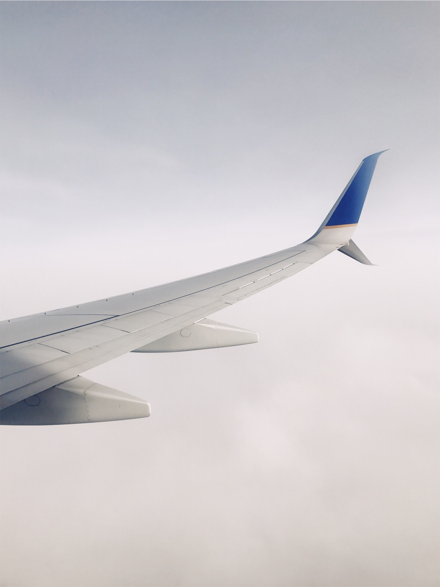 A view from an airplane window on the plane's wing and thick clouds below