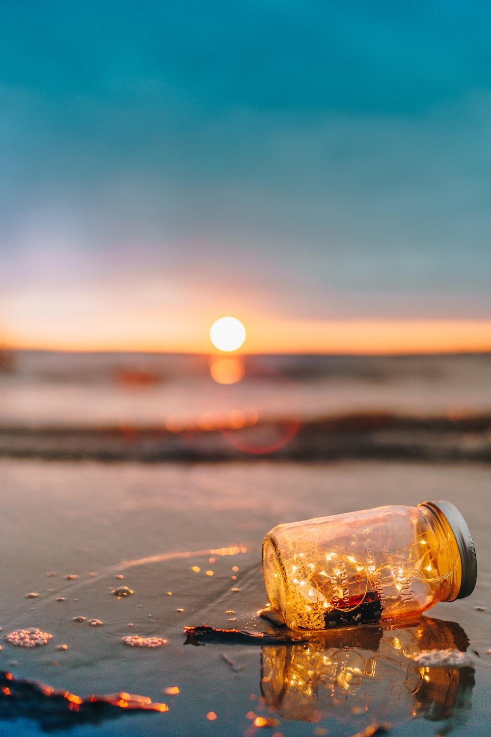 clear glass mason jar on beach during sunset