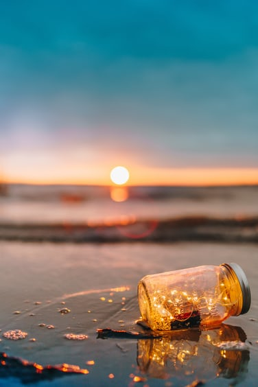 Fairy Lights In A Mason Jar On Wet Sandy Beach At Sunset
